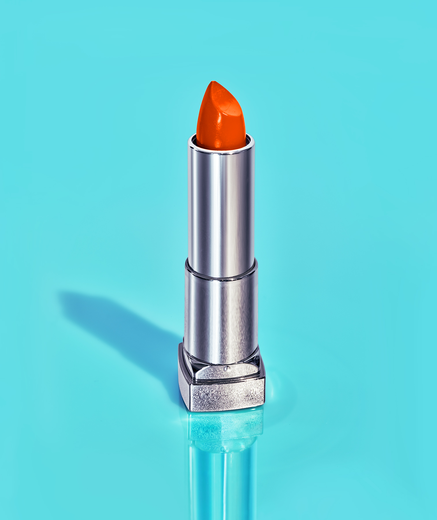 Bright coral lipstick on turquoise