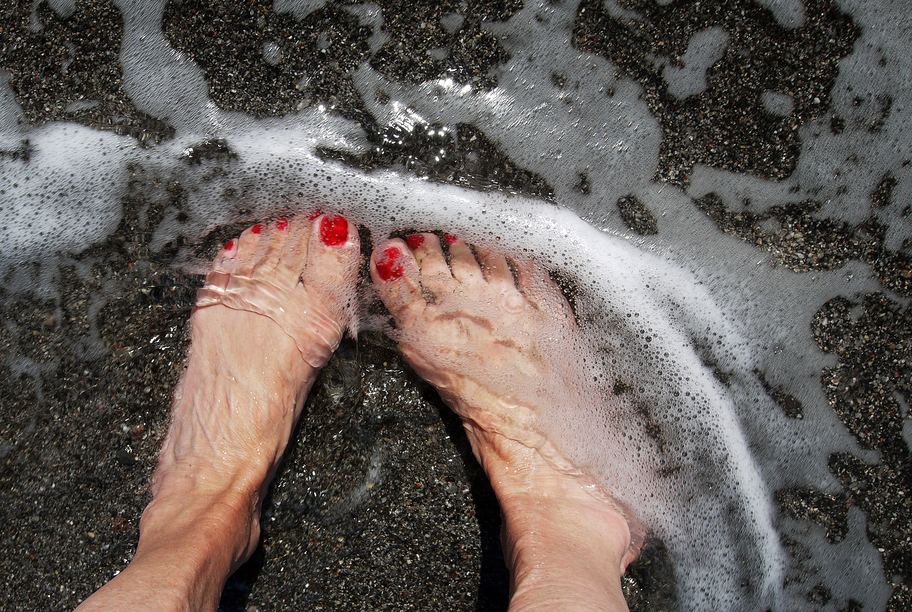 Feet in water at black sand beach