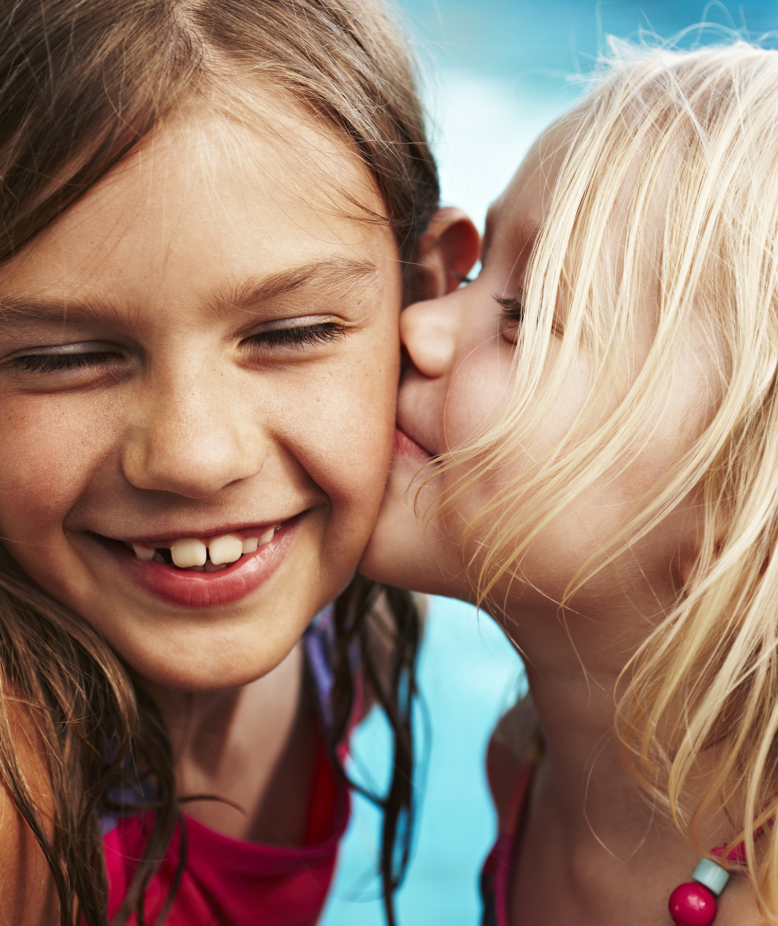Sister kisses sister's cheek by the pool