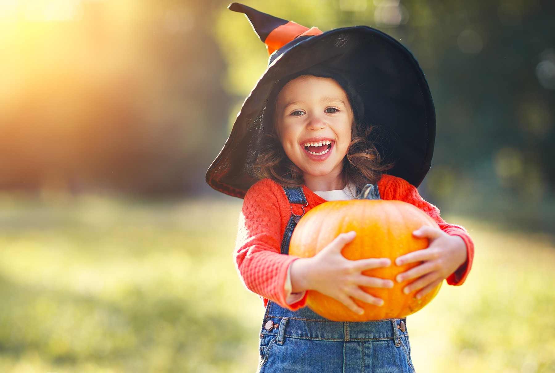 Girl in witch hat with pumpkin