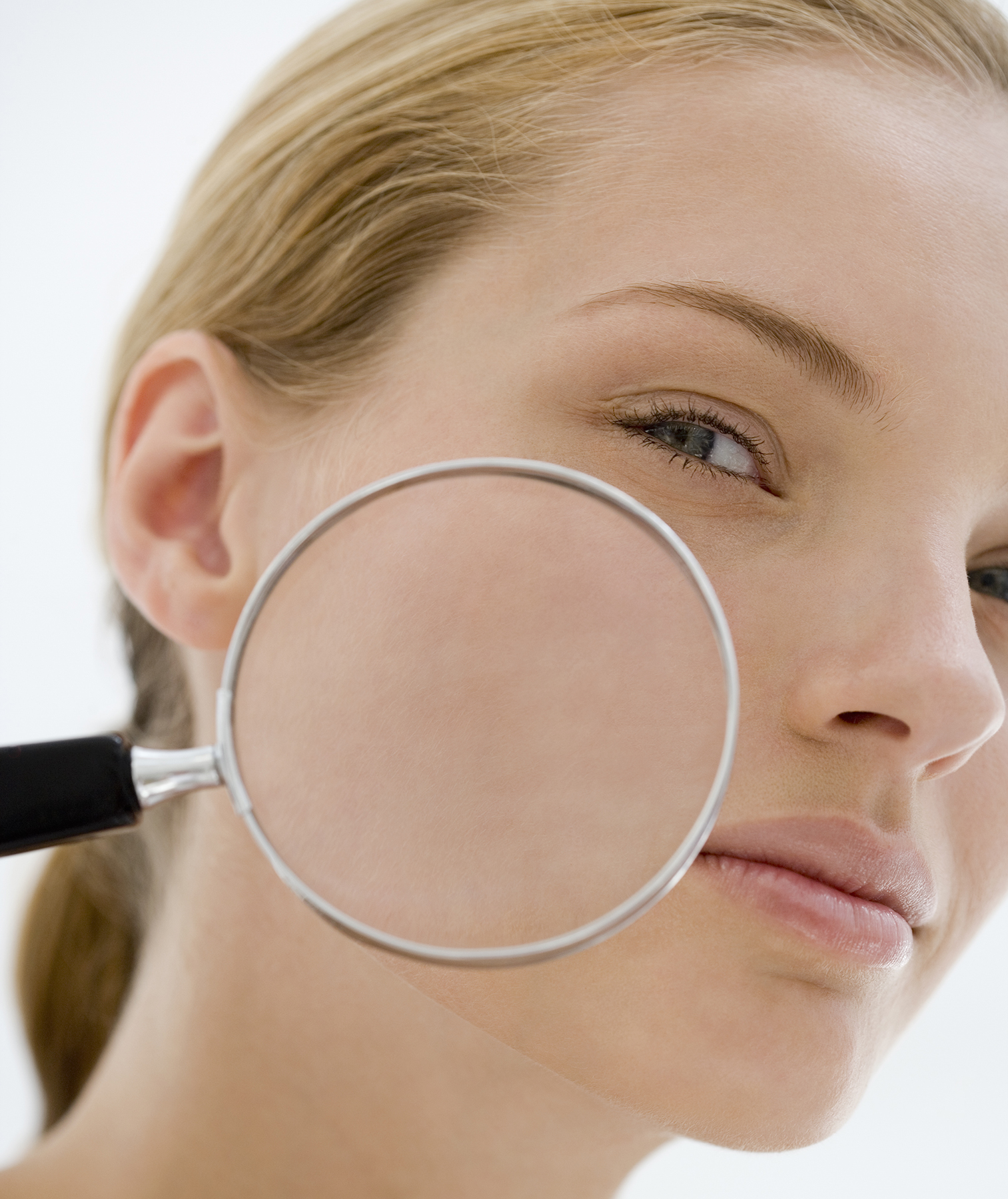 Woman with magnifying glass on skin