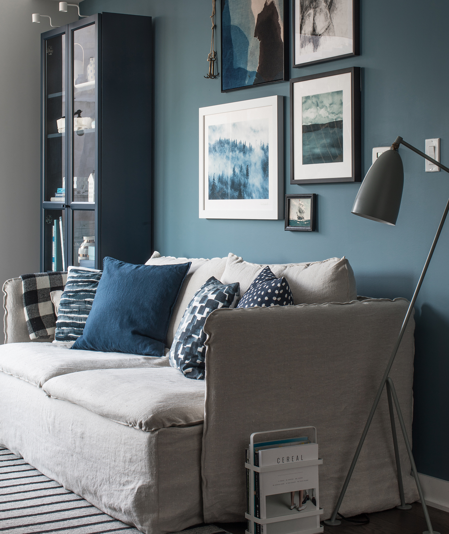Blue and gray living room with art and throw pillows