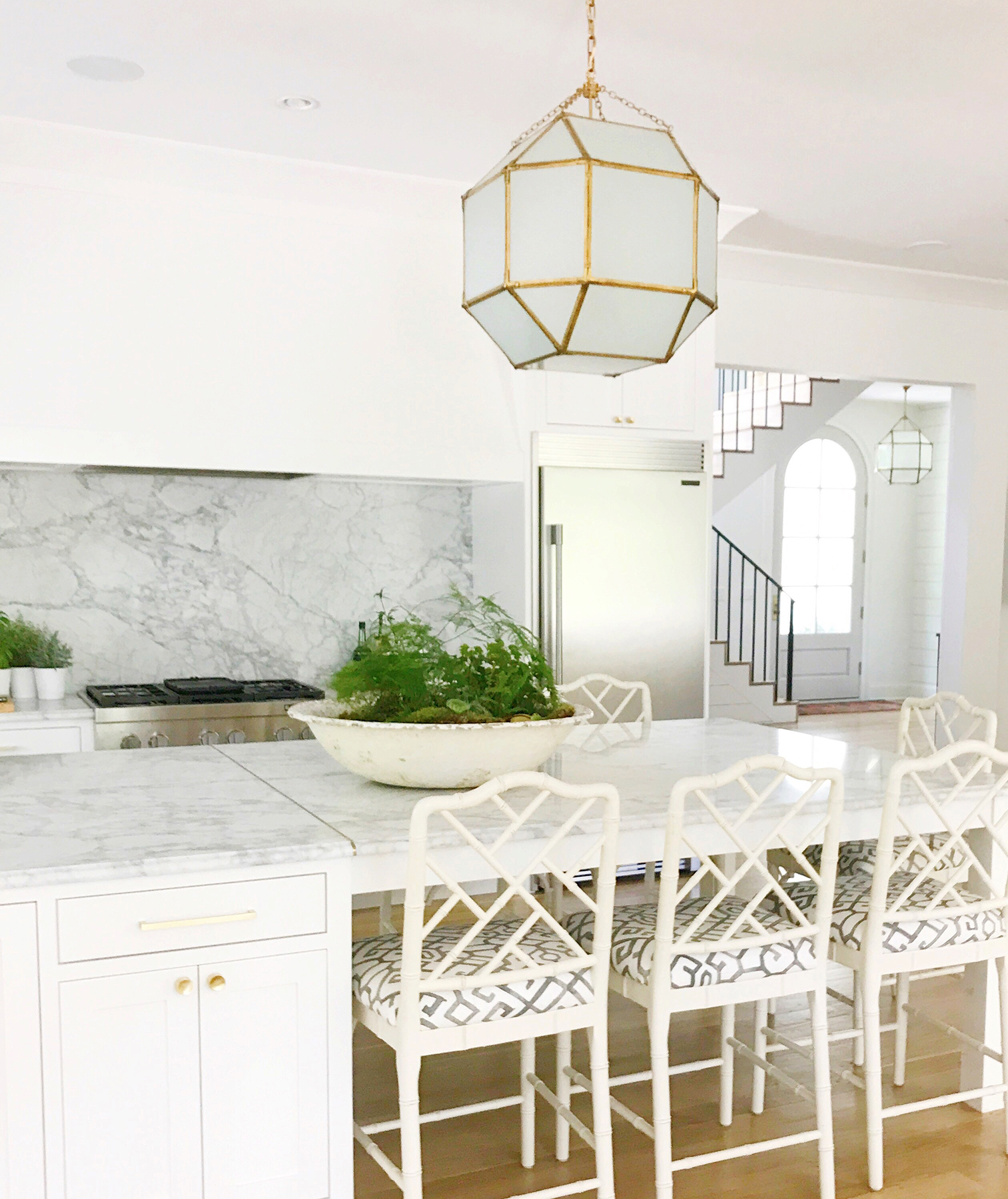 White and marble kitchen with large light fixture