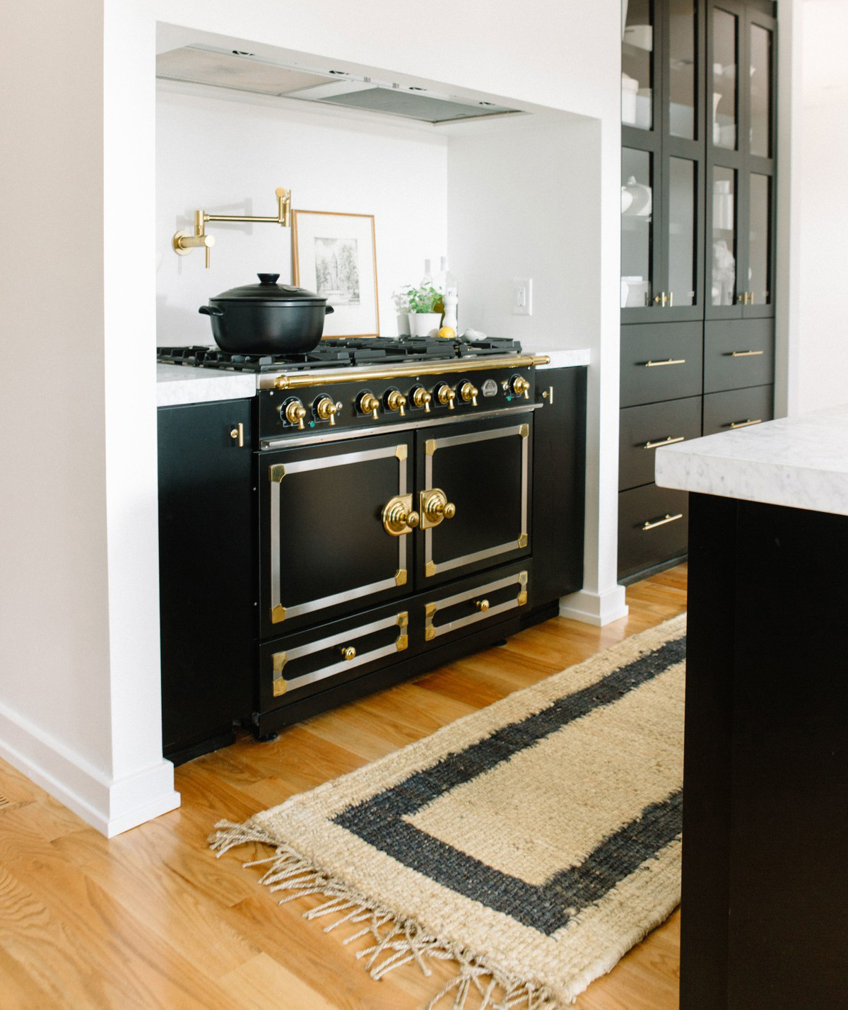 Kitchen with black stove and woven rug