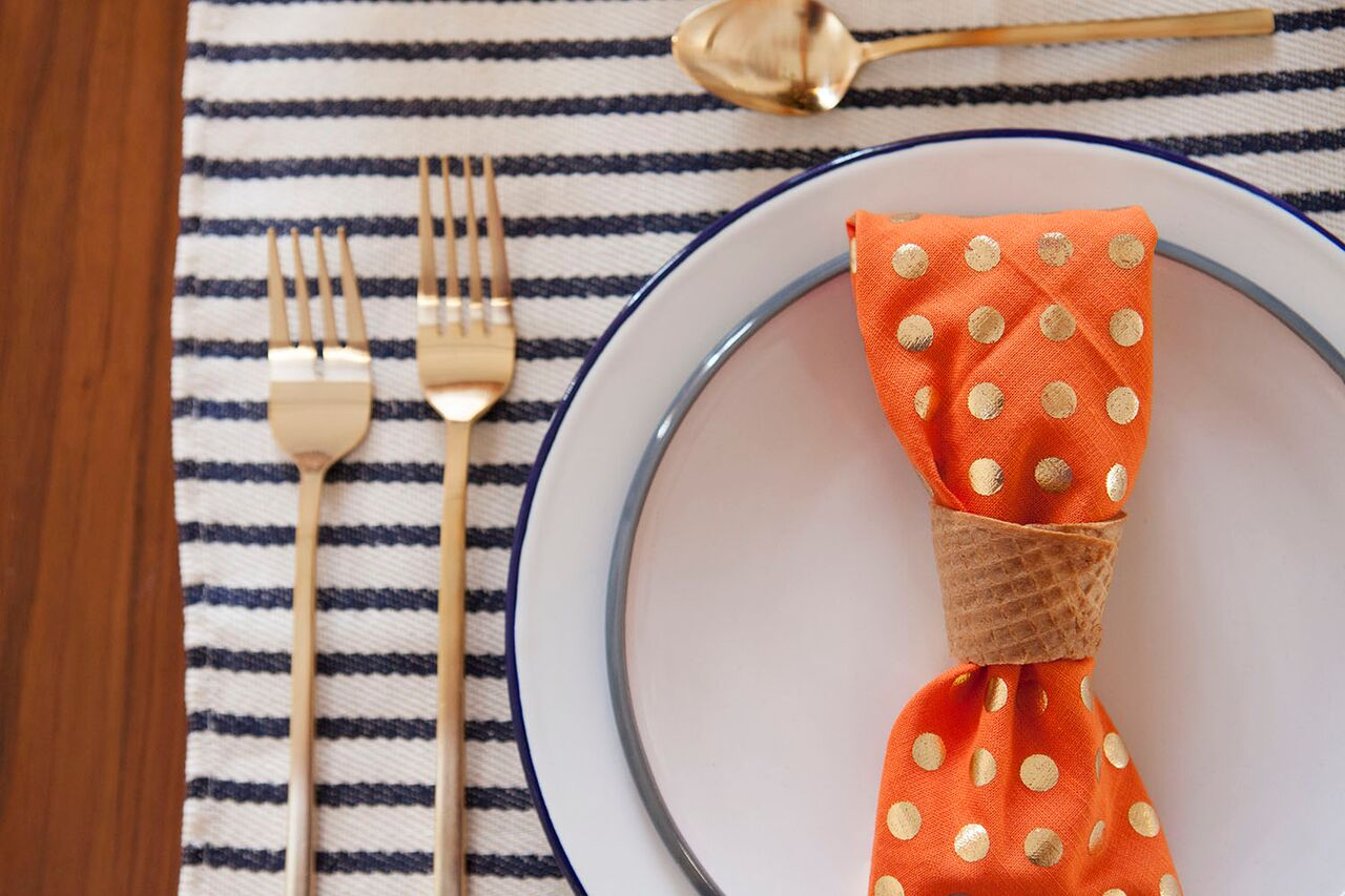 Thanksgiving place setting with dotted napkin and striped placemat