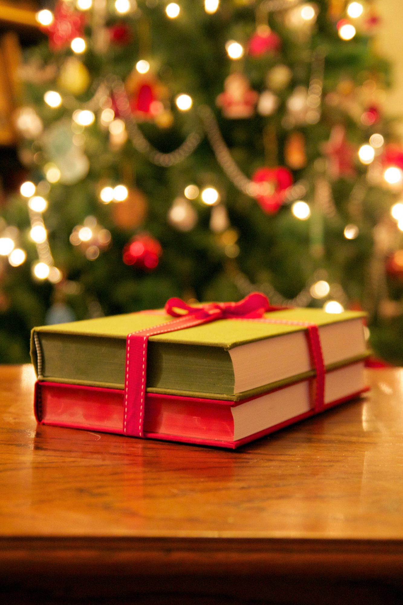 Books tied with ribbon near Christmas tree