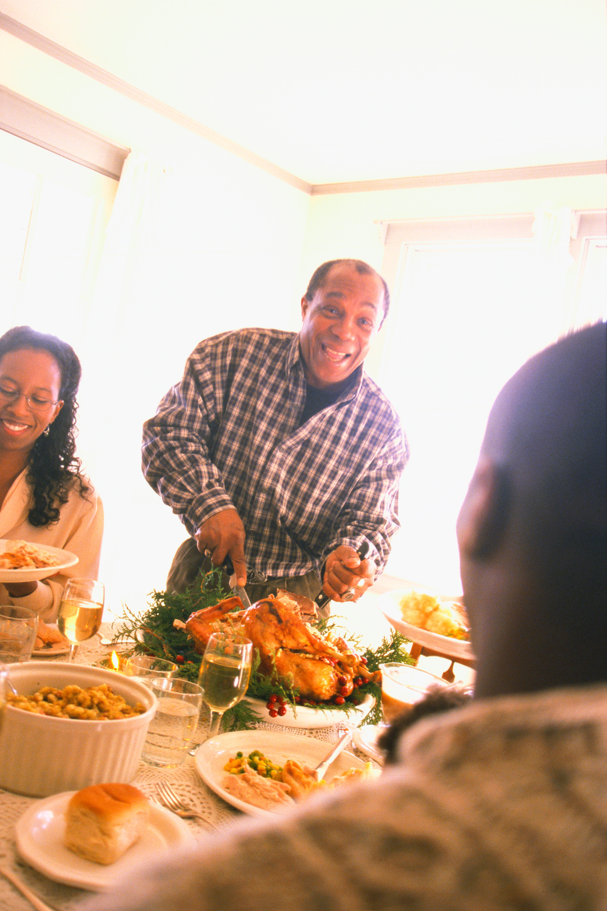 Man carving turkey at family dinner