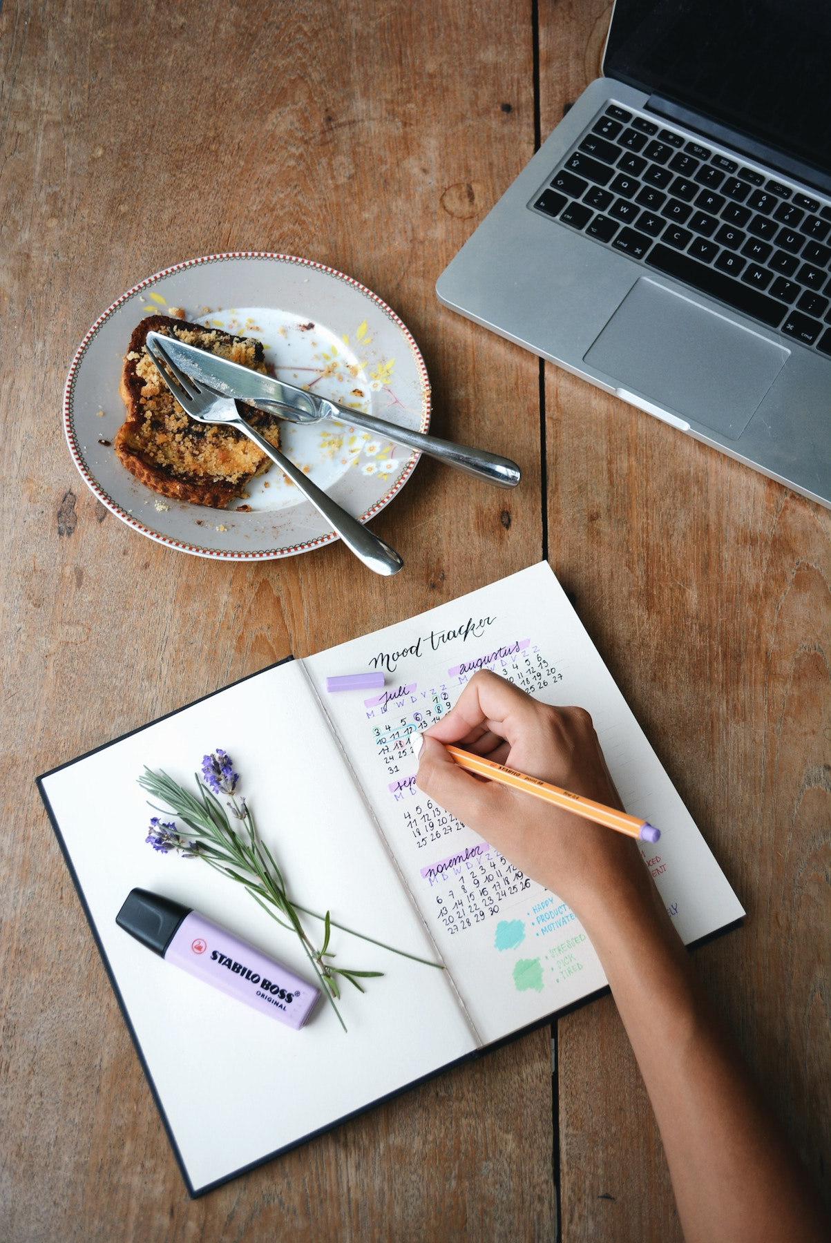 Productivity journal, computer, and markers on wood table
