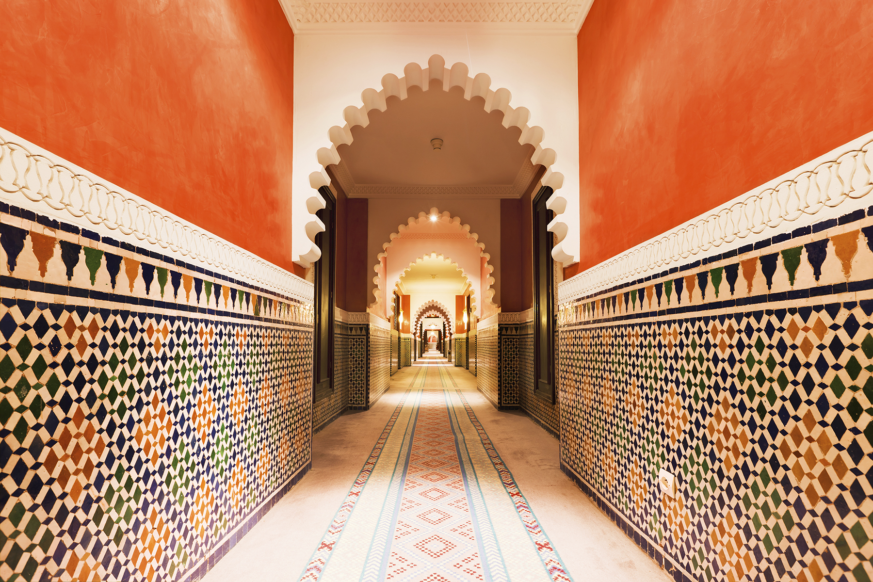 Orange-painted Moroccan archway with ornamental tiles