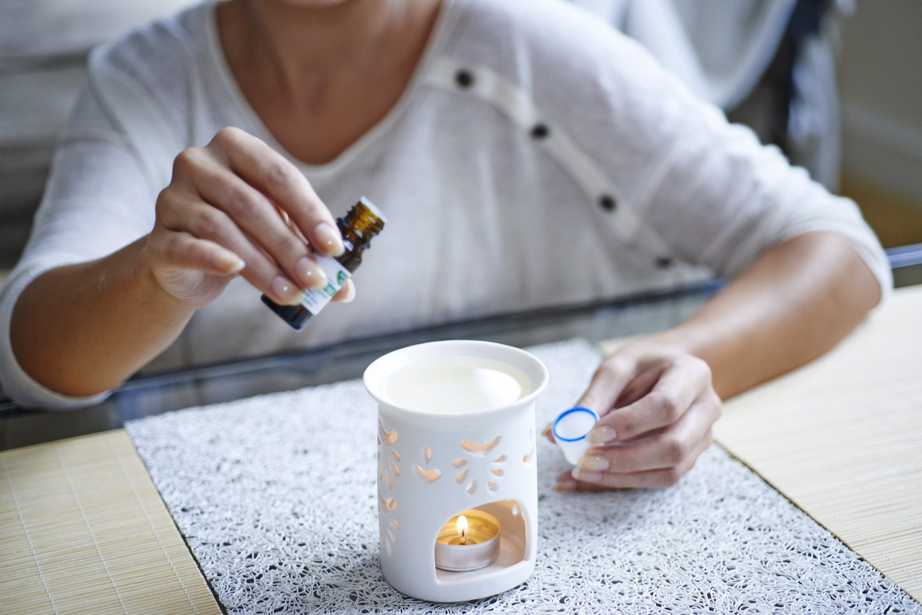 Woman adding Essential Oil to diffuer