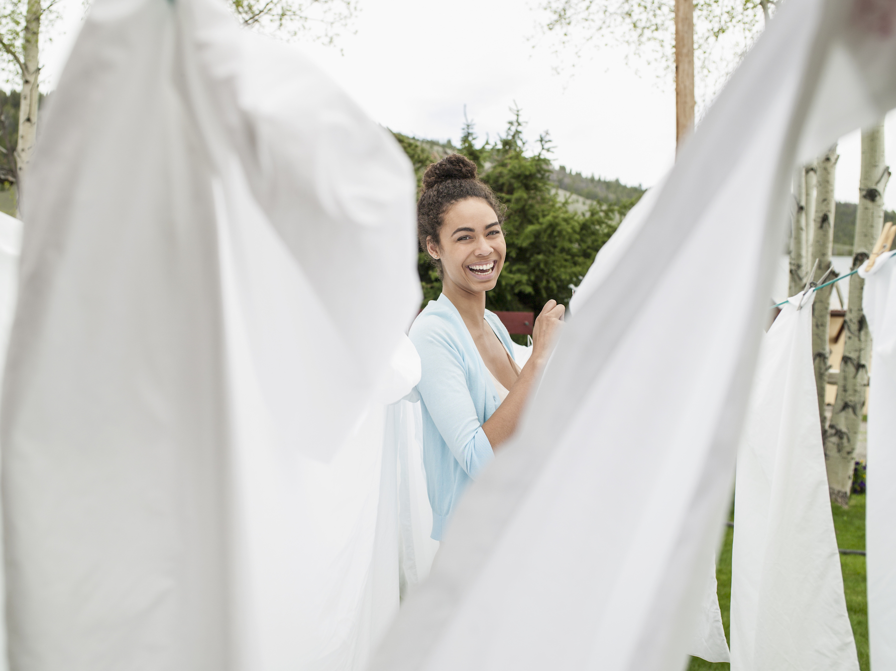 Woman hanging sheets outside to dry