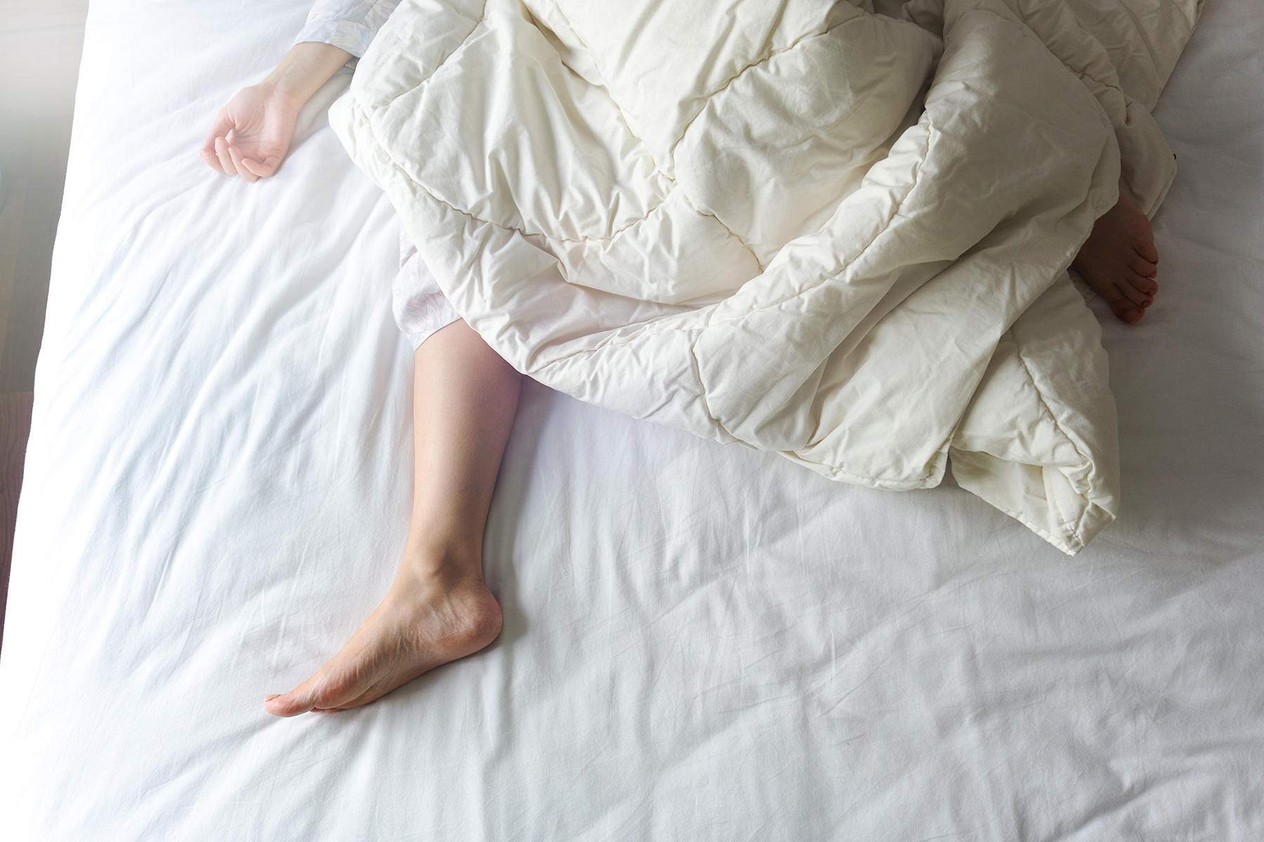 Woman under comforter on mattress
