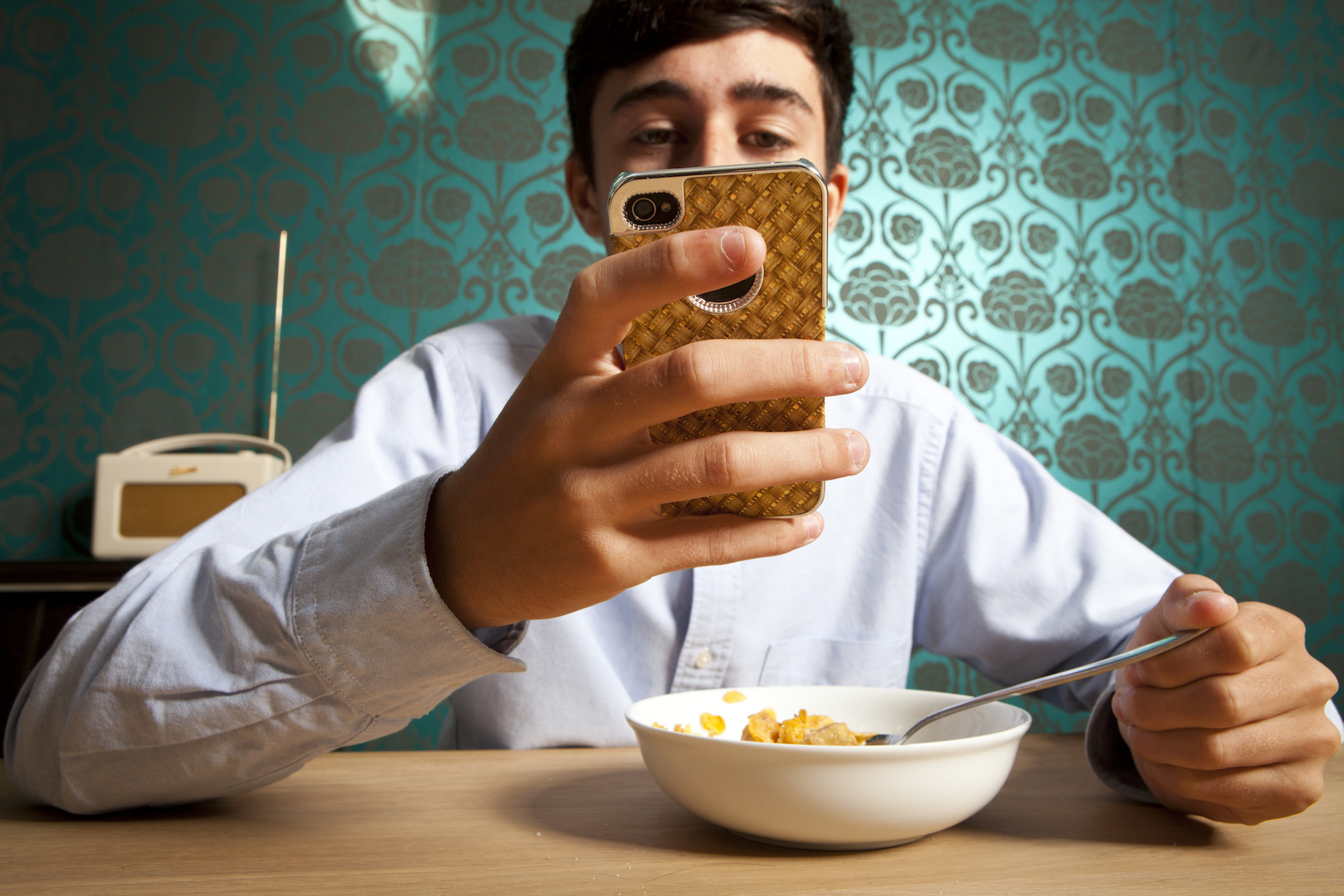 Teen boy with phone at breakfast