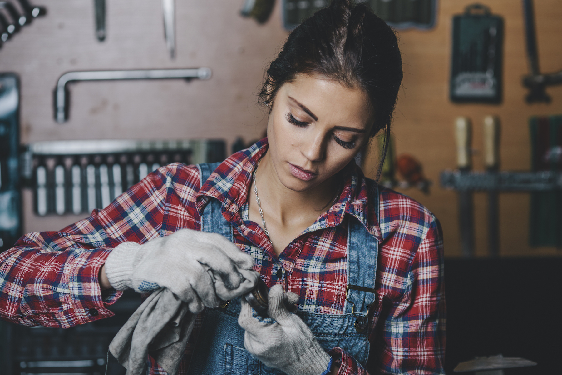 Woman mechanic cleaning metal part
