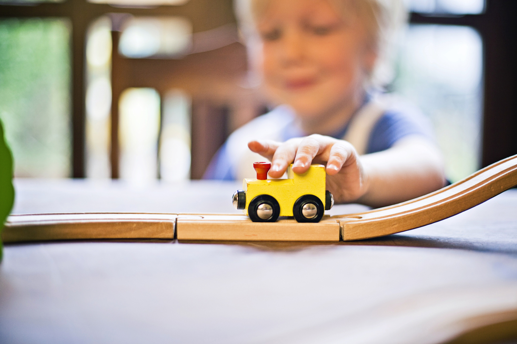 Child with yellow toy train