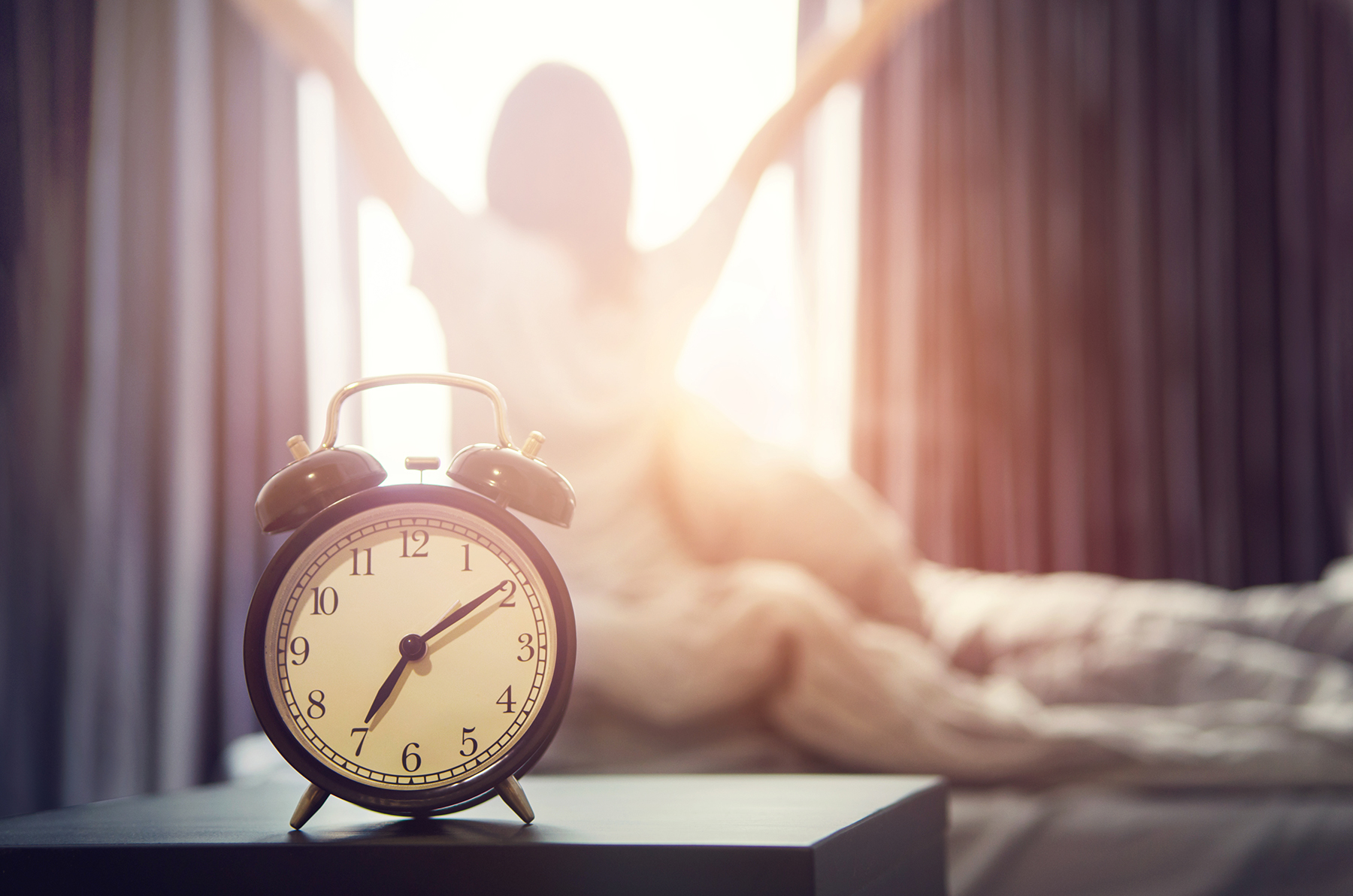 Woman waking up, alarm clock in foreground