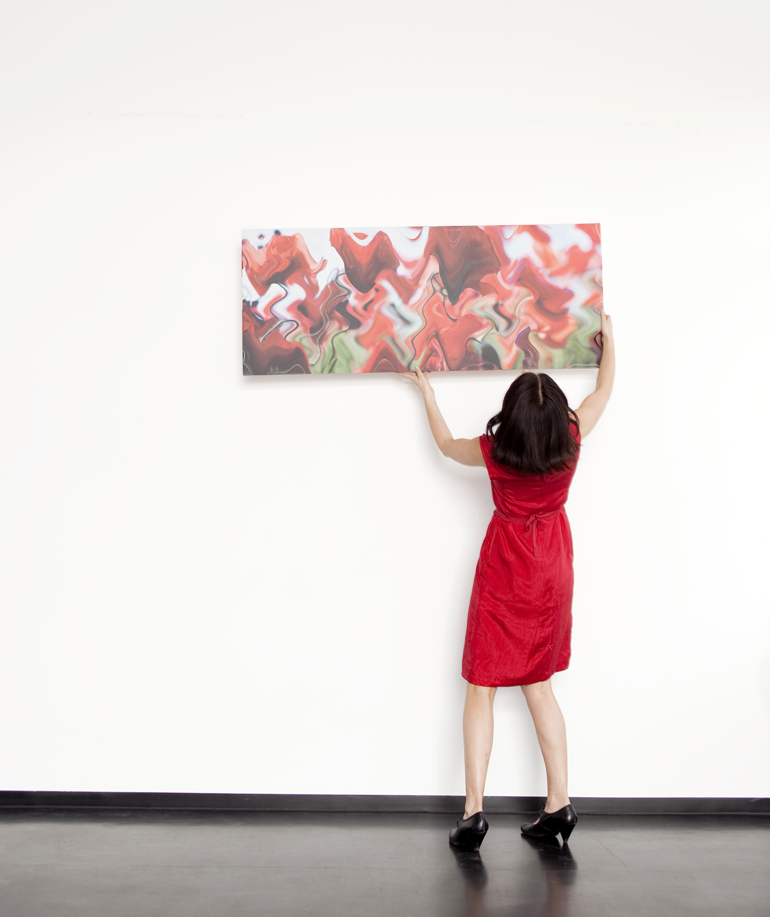 Woman in red dress hanging piece of art