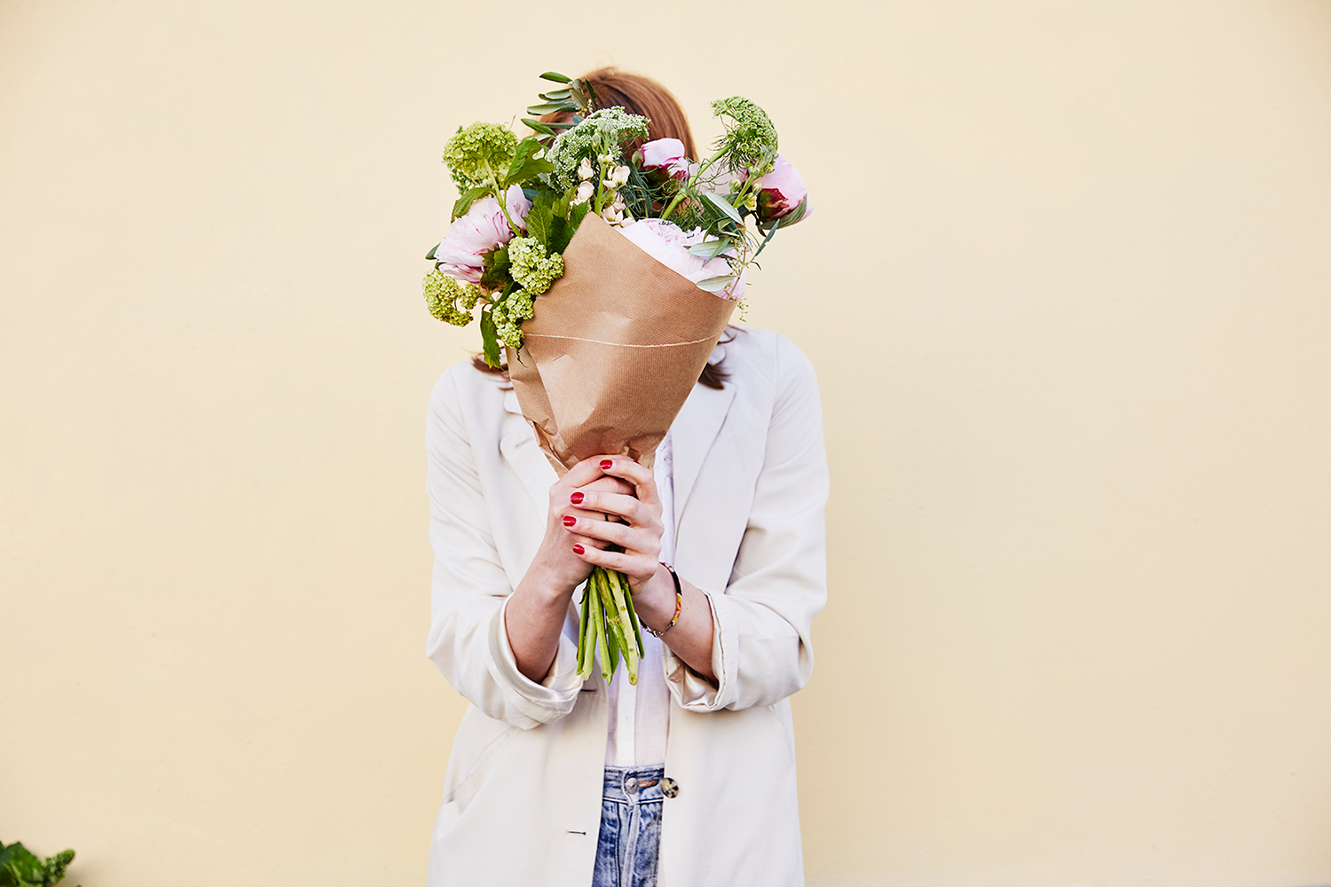 Woman Holding Pink and Green Flowers in Front of Her Face