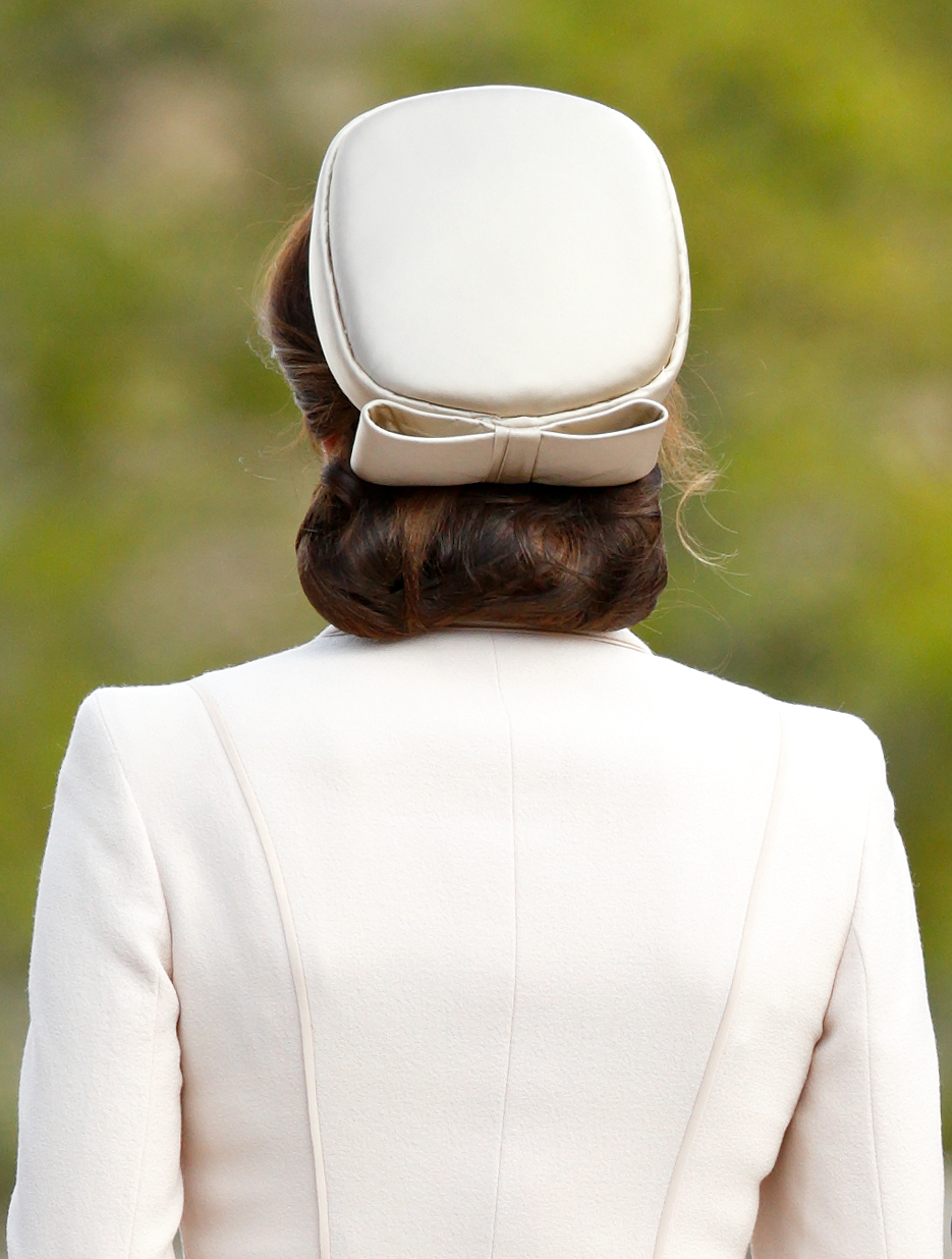 Kate Middleton wearing a bun in a hair net and a hat
