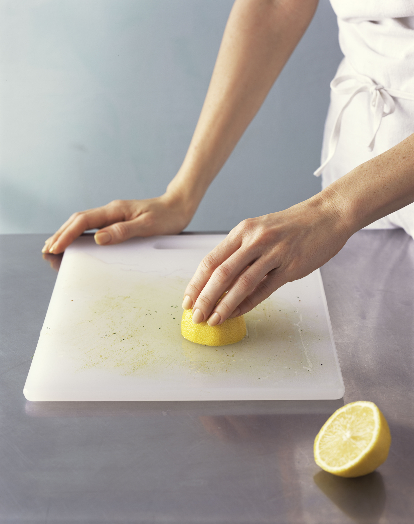 Woman Cleaning Cutting Board with Lemon