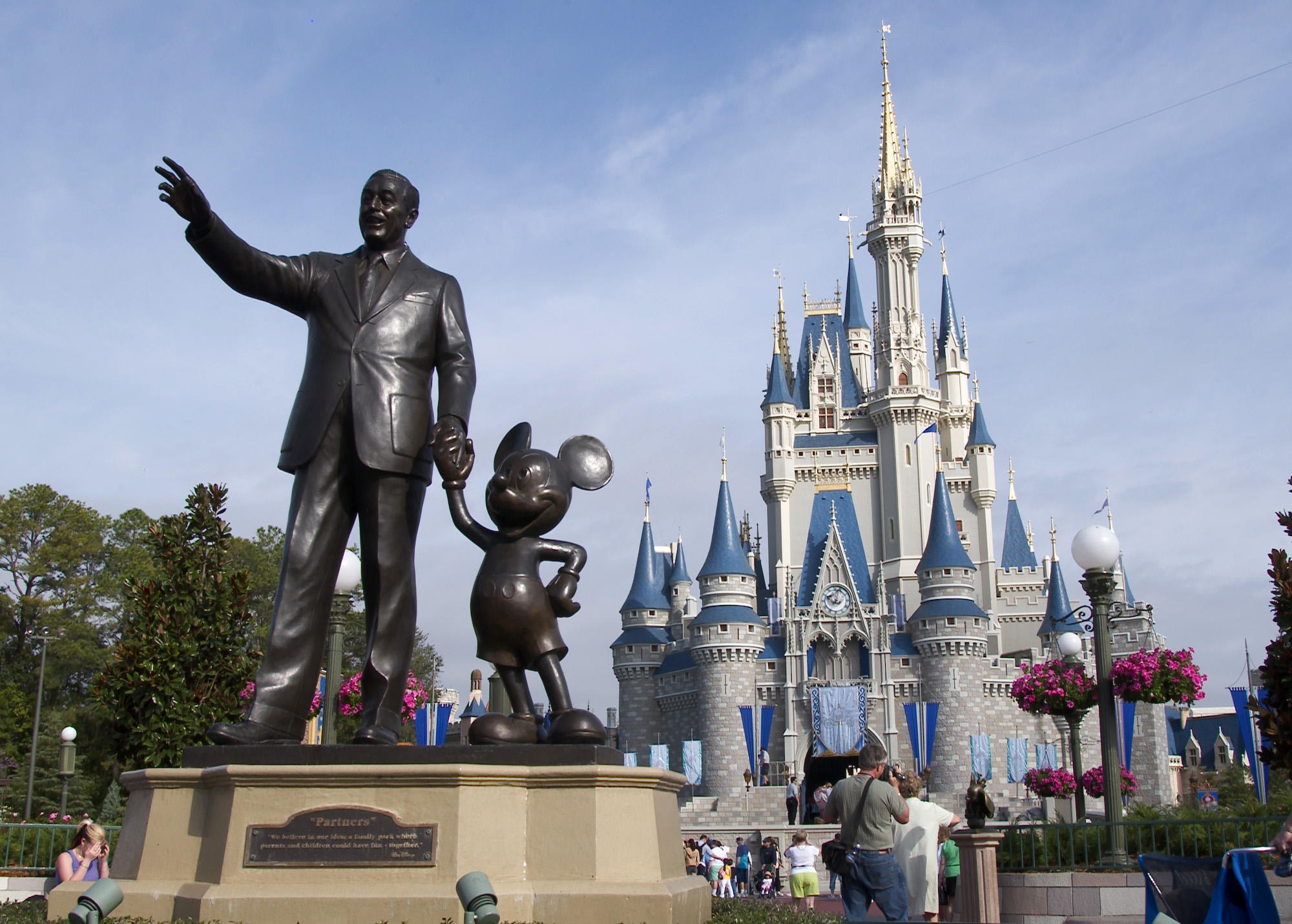A statue of Walt Disney and Mickey Mouse stands in front of the Cinderella's castle at Walt Disney World's Magic Kingdom