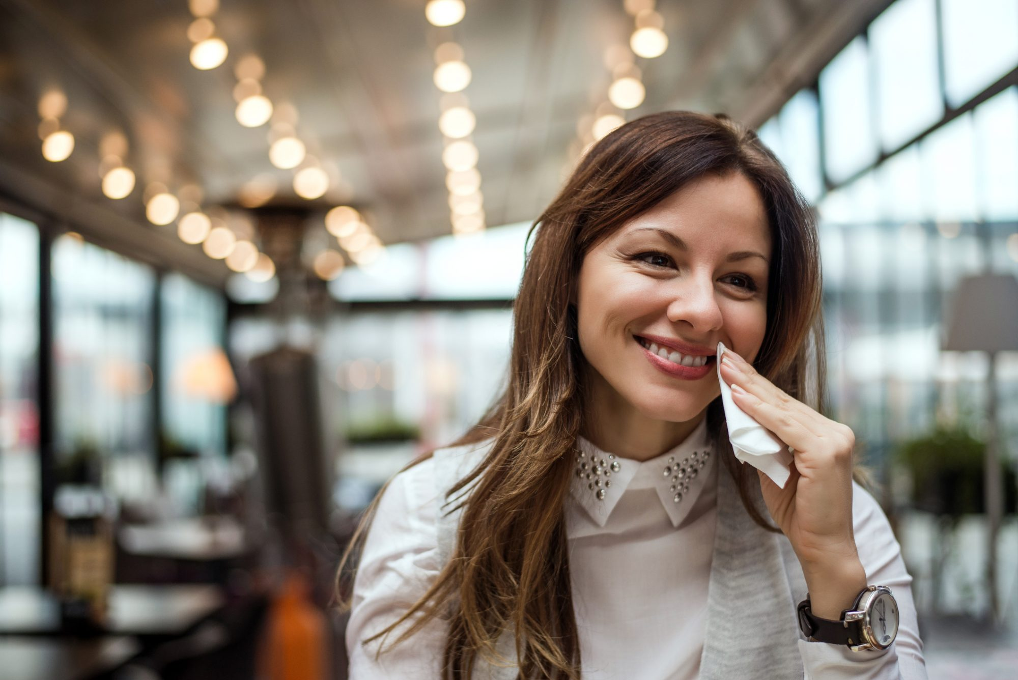 Woman wiping mouth with napkin