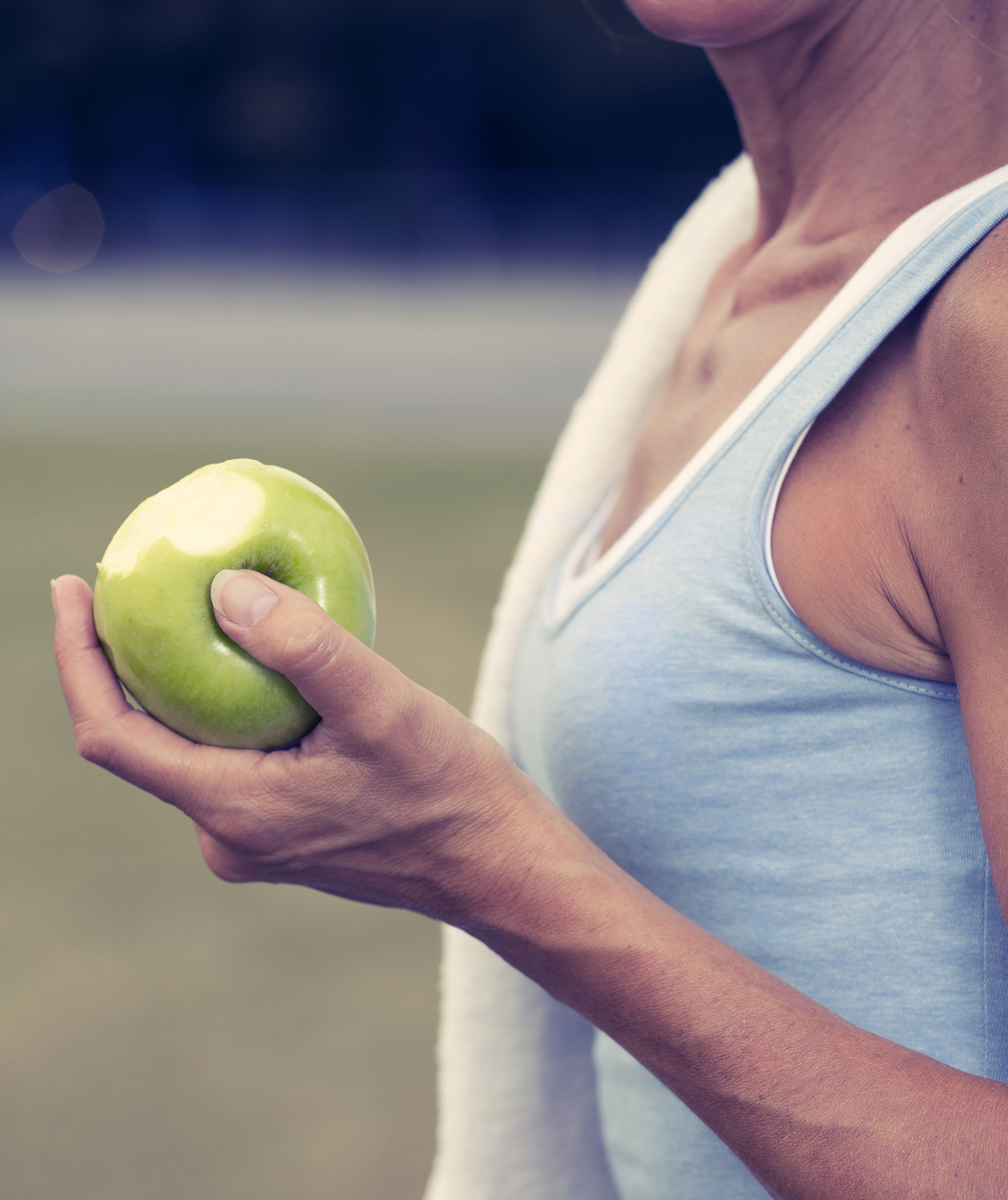 Woman with apple after exercise