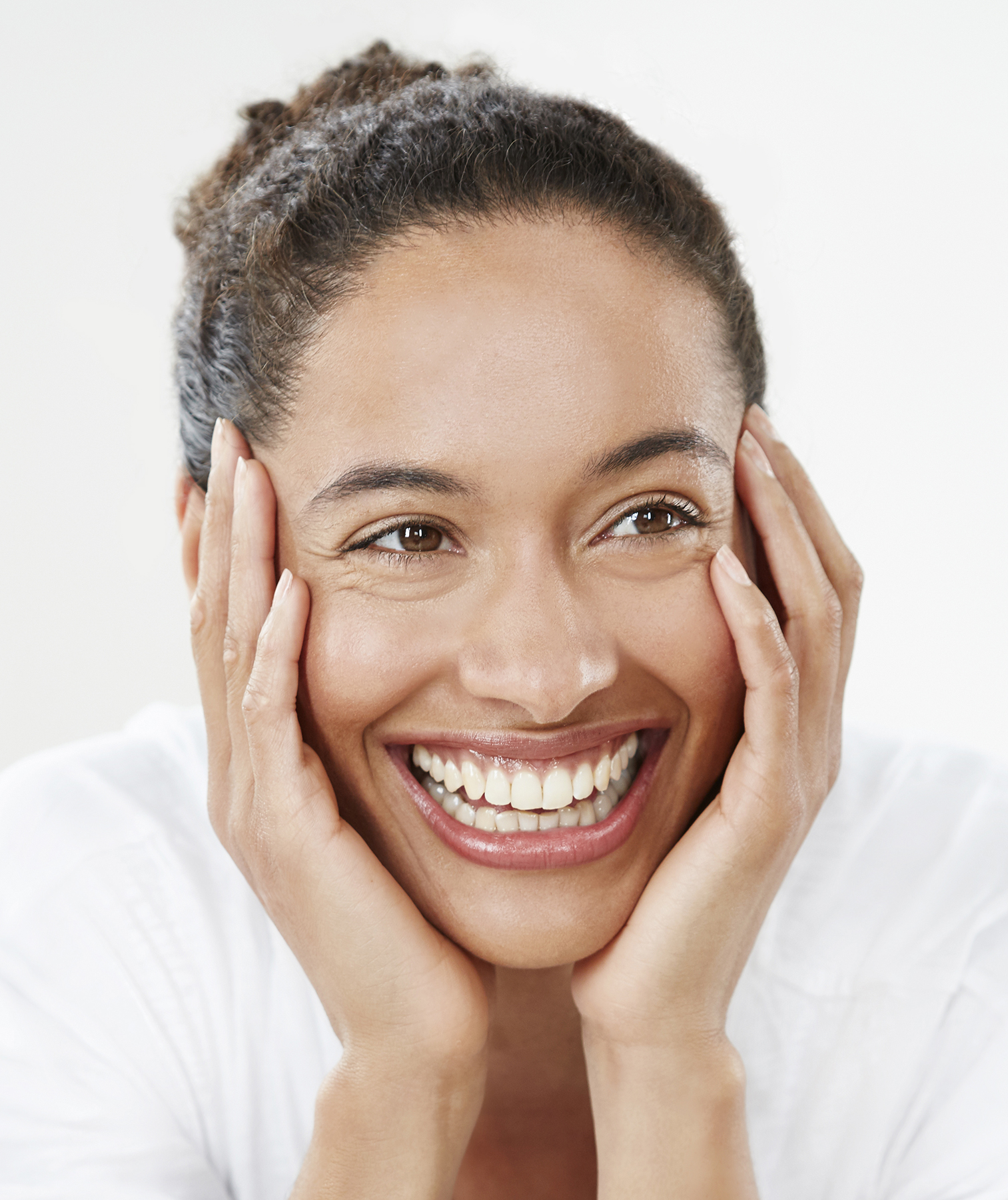 Model with hair pulled back, smiling and holding face in hands