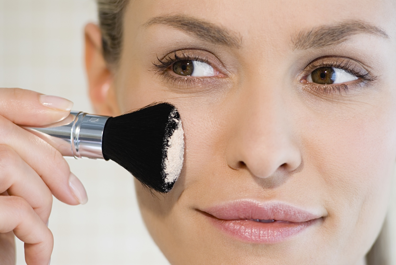 A Woman Applying Translucent Setting Powder Over Her Makeup