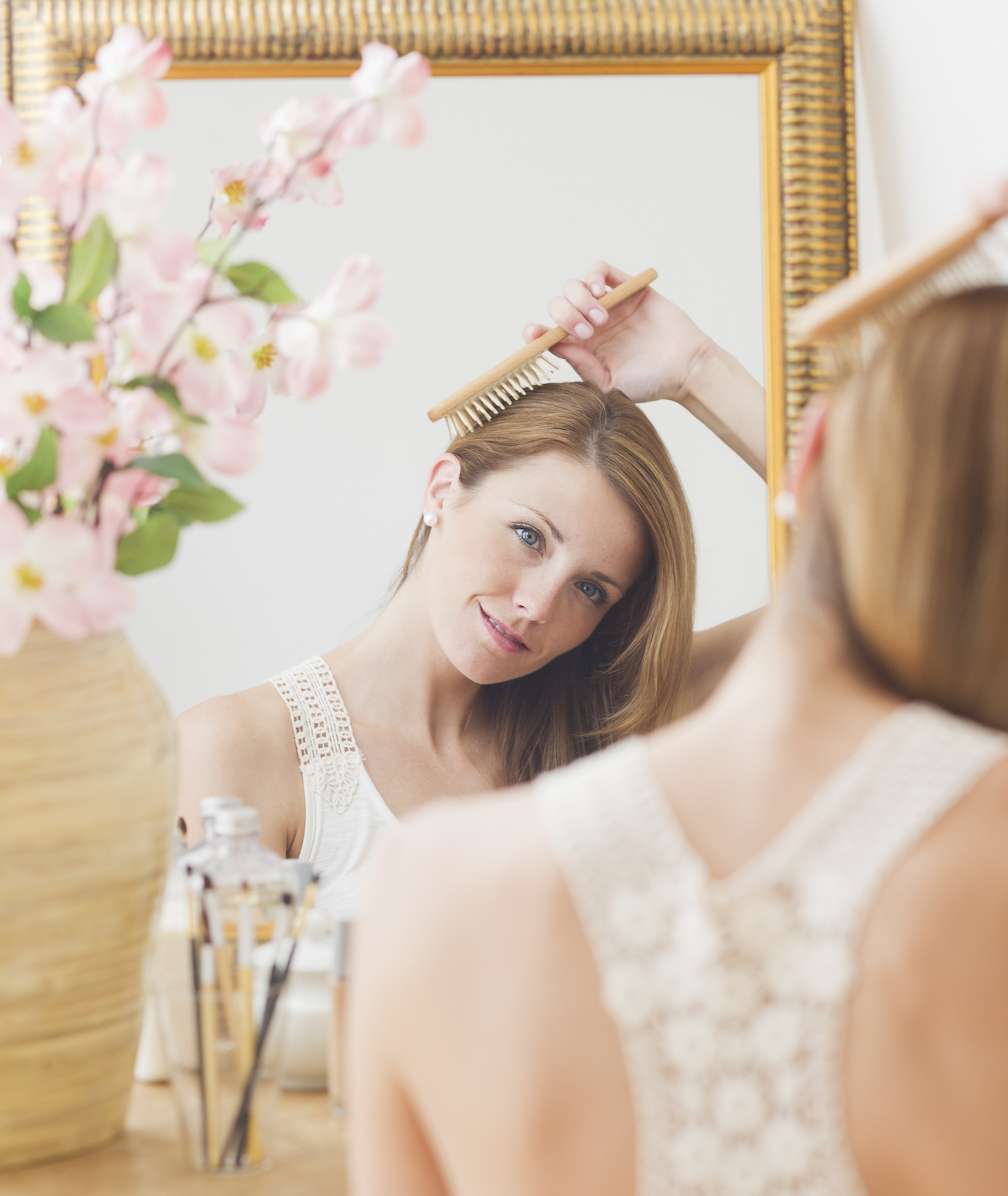 Woman brushing hair in front of mirror