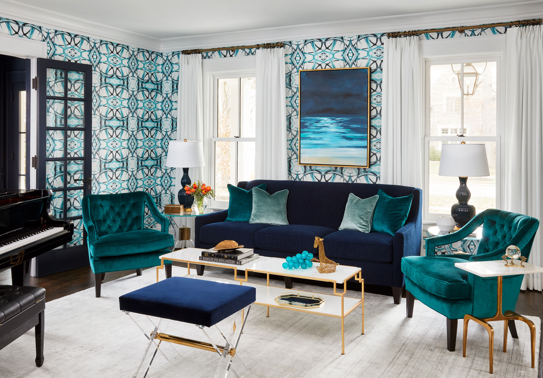 The foyer connects to a formal living space, which the homeowners use for entertaining. Both rooms are rich with blue tones.