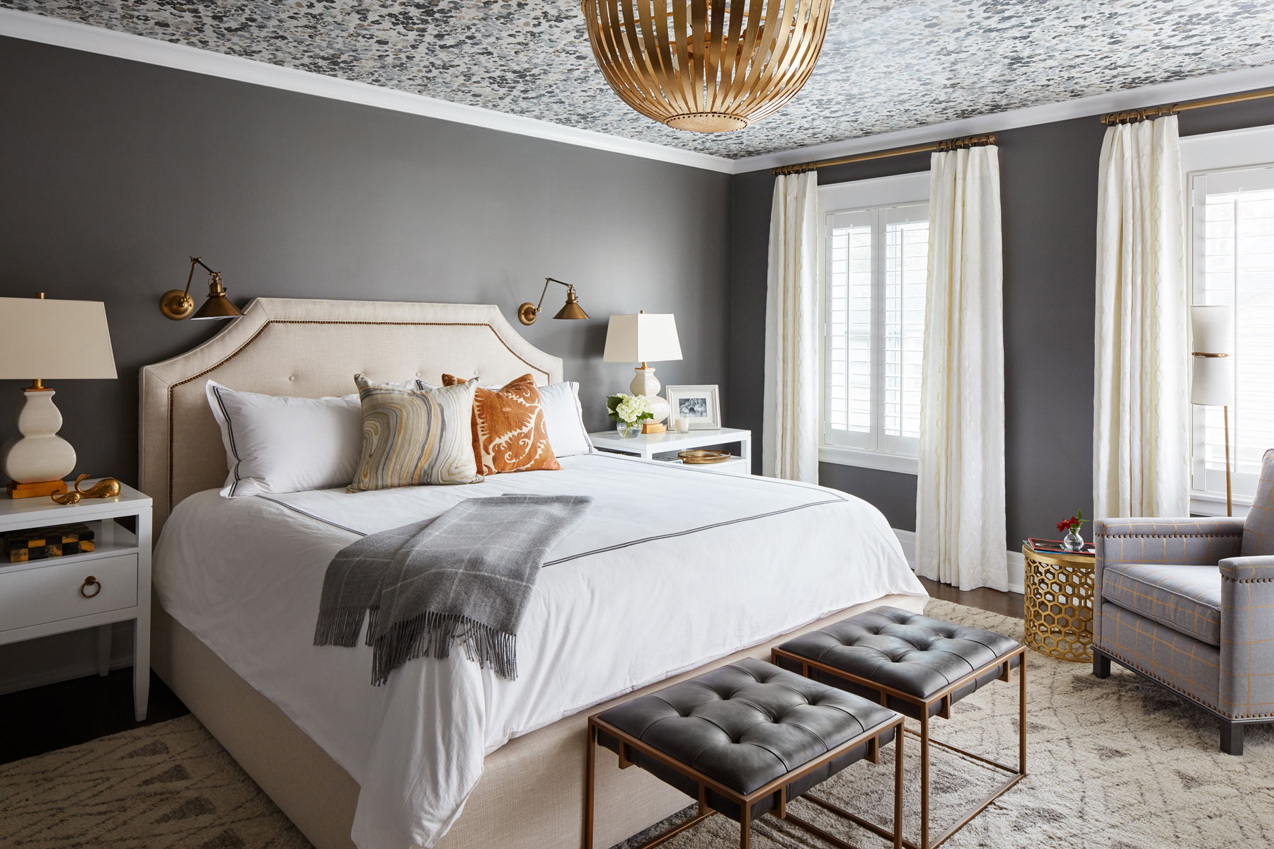 Neutral furnishings help balance the surrounding deep colors, while flashes of gold help unite the room with the rest of the home and flowing white curtains keep it from feeling heavy and dark.
