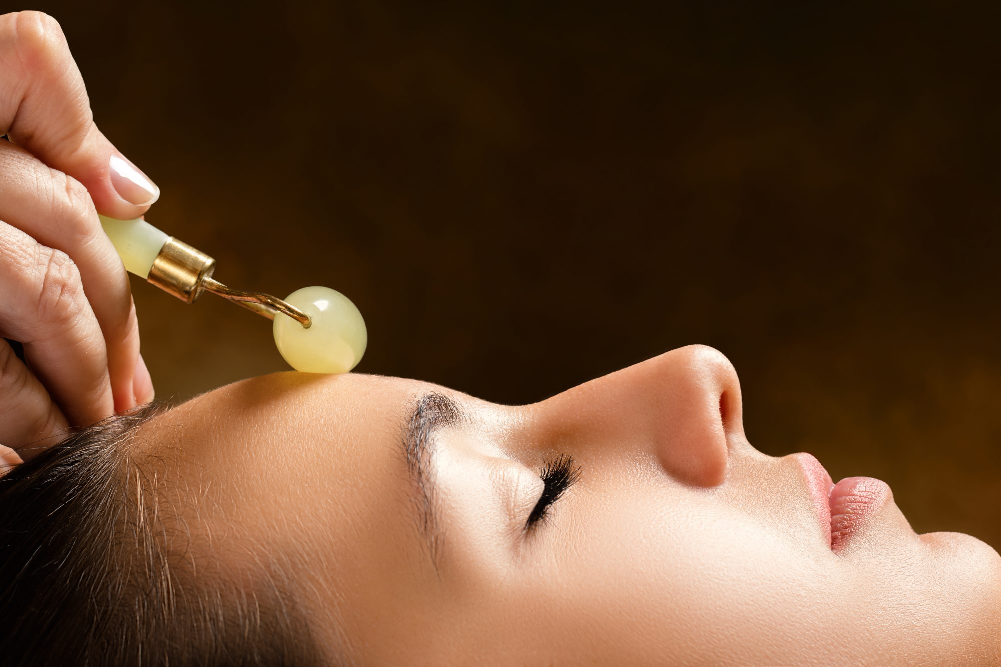 A Woman Using a Jade Roller on Her Face