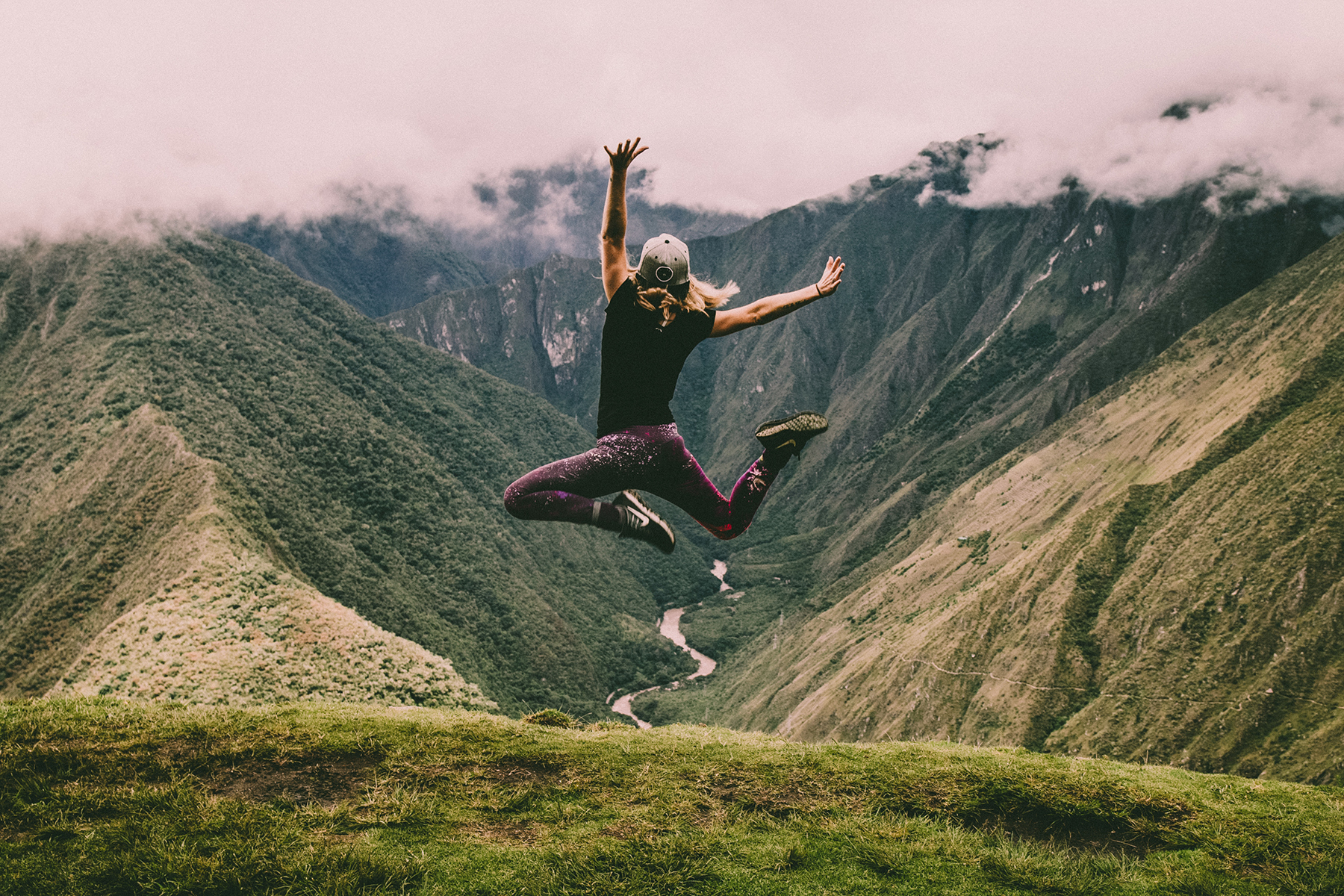Young woman on a hike on the Inca Trail jumping