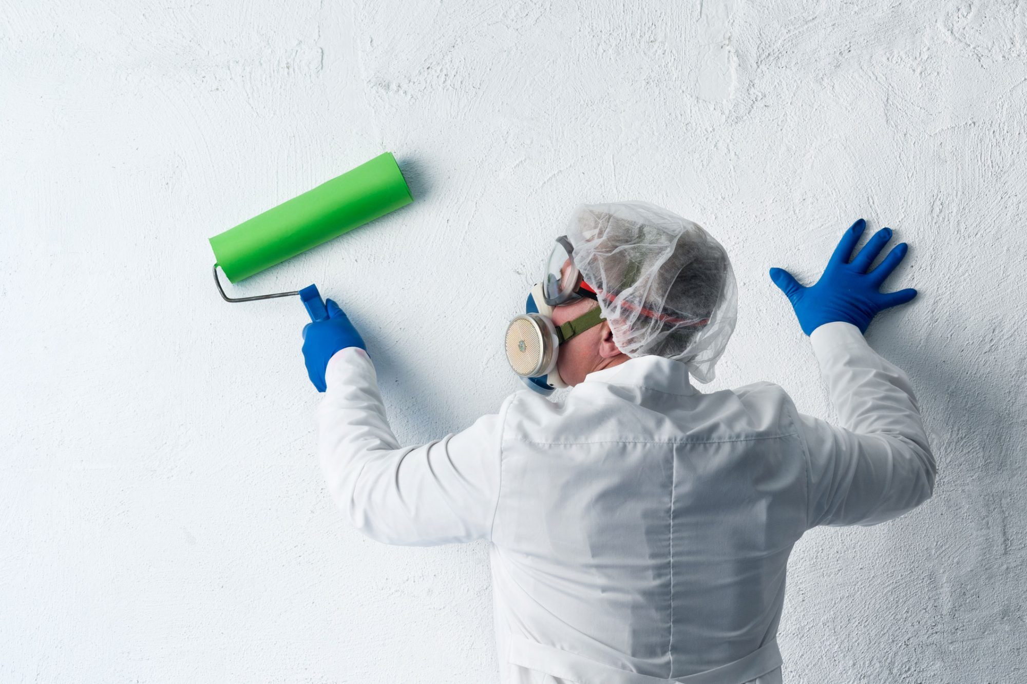 Man fixing lead paint wall with paint, mask, and gloves