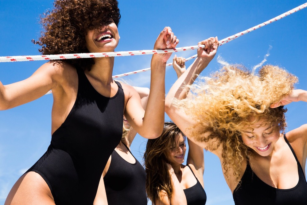 Four Women Wearing Black One Piece Swimsuits