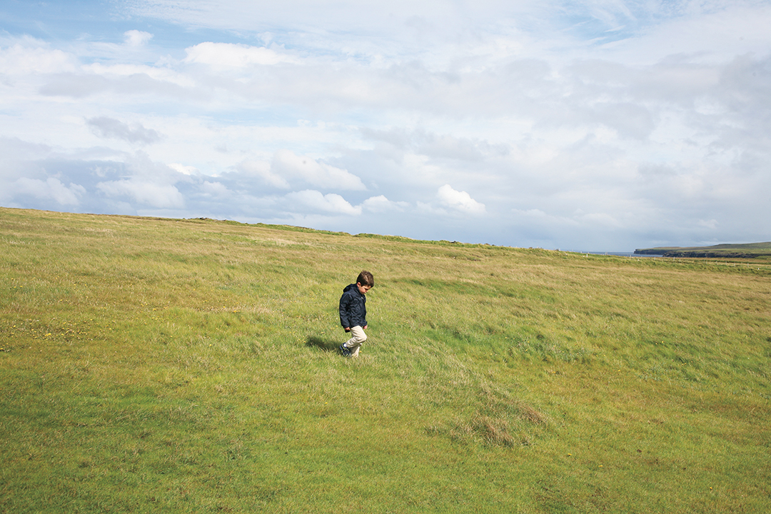 boy walking through grass ireland