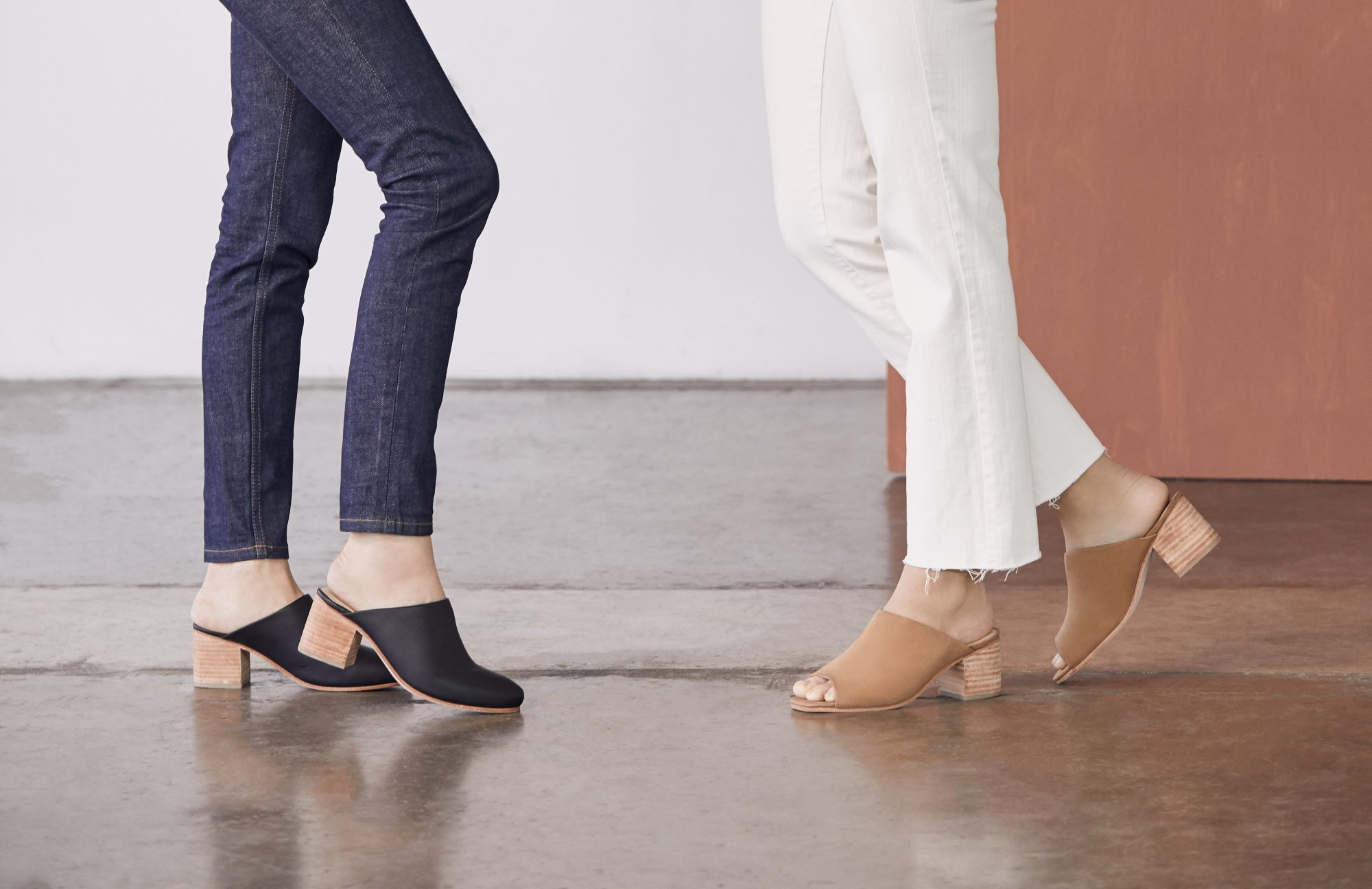 Two sets of legs from waist down wearing nisolo mules