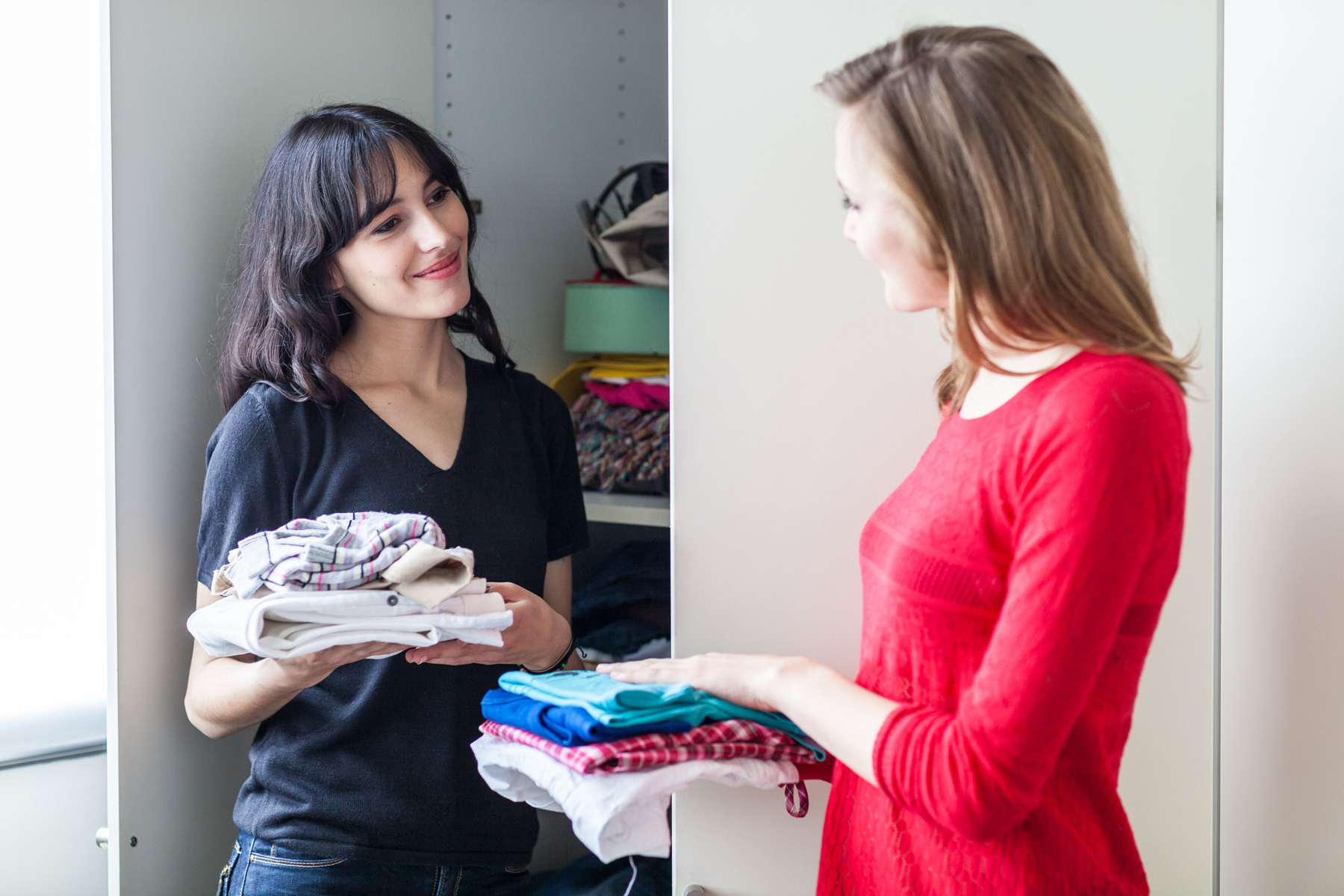 Woman working with a professional organizer to organize her closet