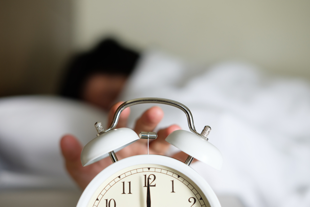 What to Know About Daylight Saving Time and Your Health: woman turning off alarm clock