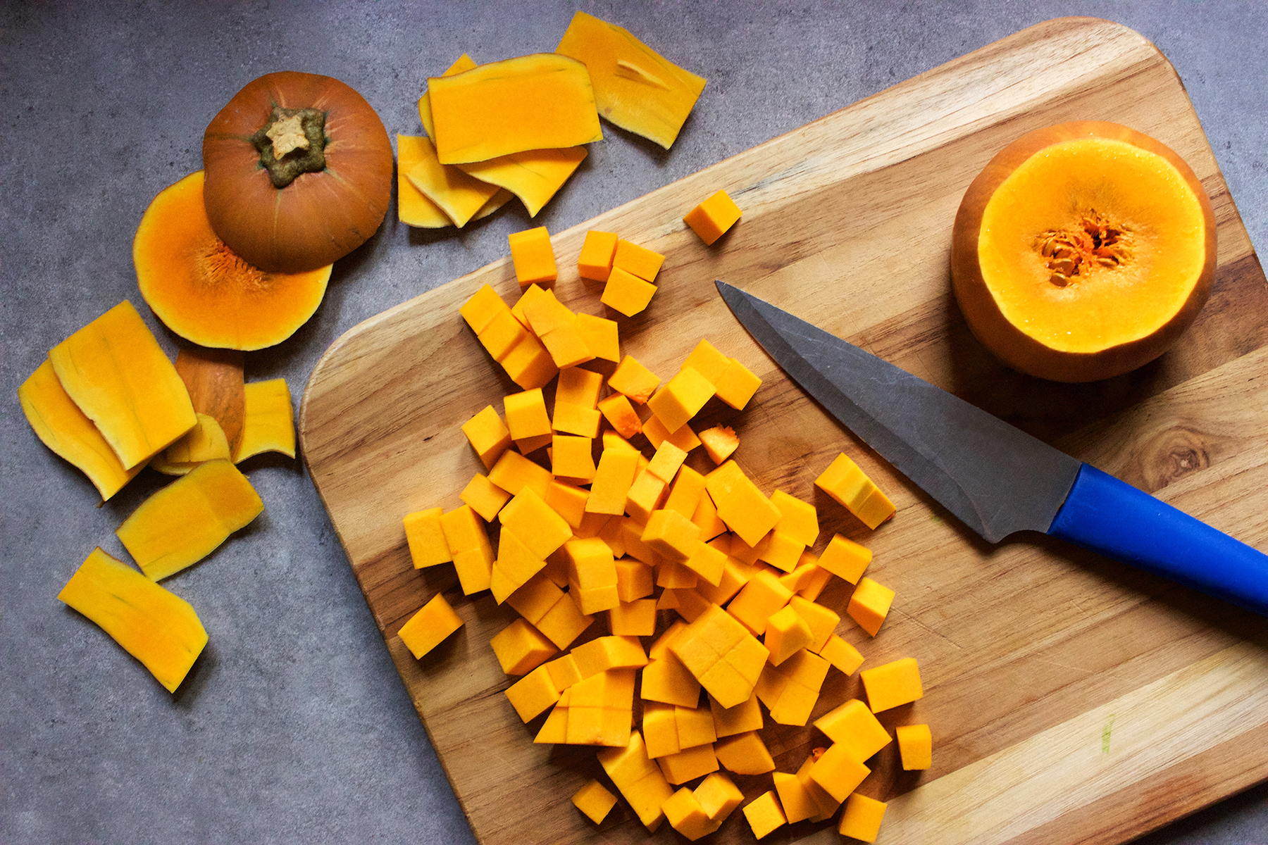 In a home kitchen, a butternut squash is being peeled and chopped into cubes on a wooden cutting board with a knife with a blue handle. Fresh vegetables, from-scratch cooking, nutrition, healthy eating.