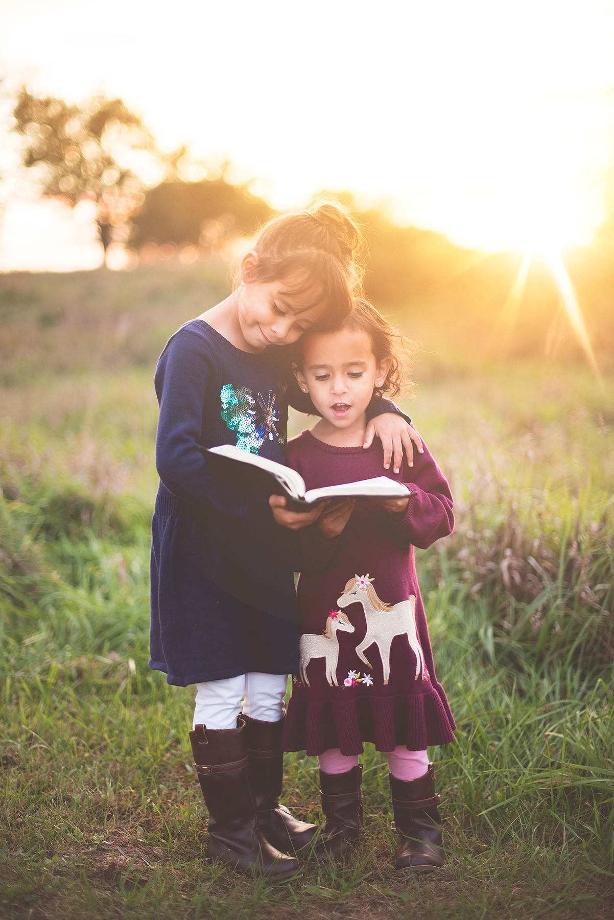 Two little girls reading a book as sun is setting