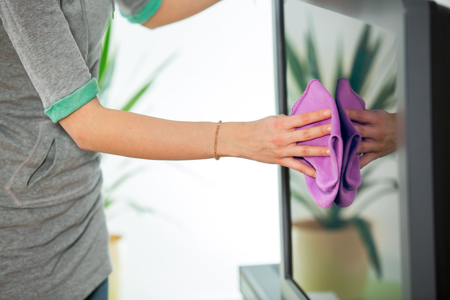 Woman cleaning a flat screen TV with a cloth