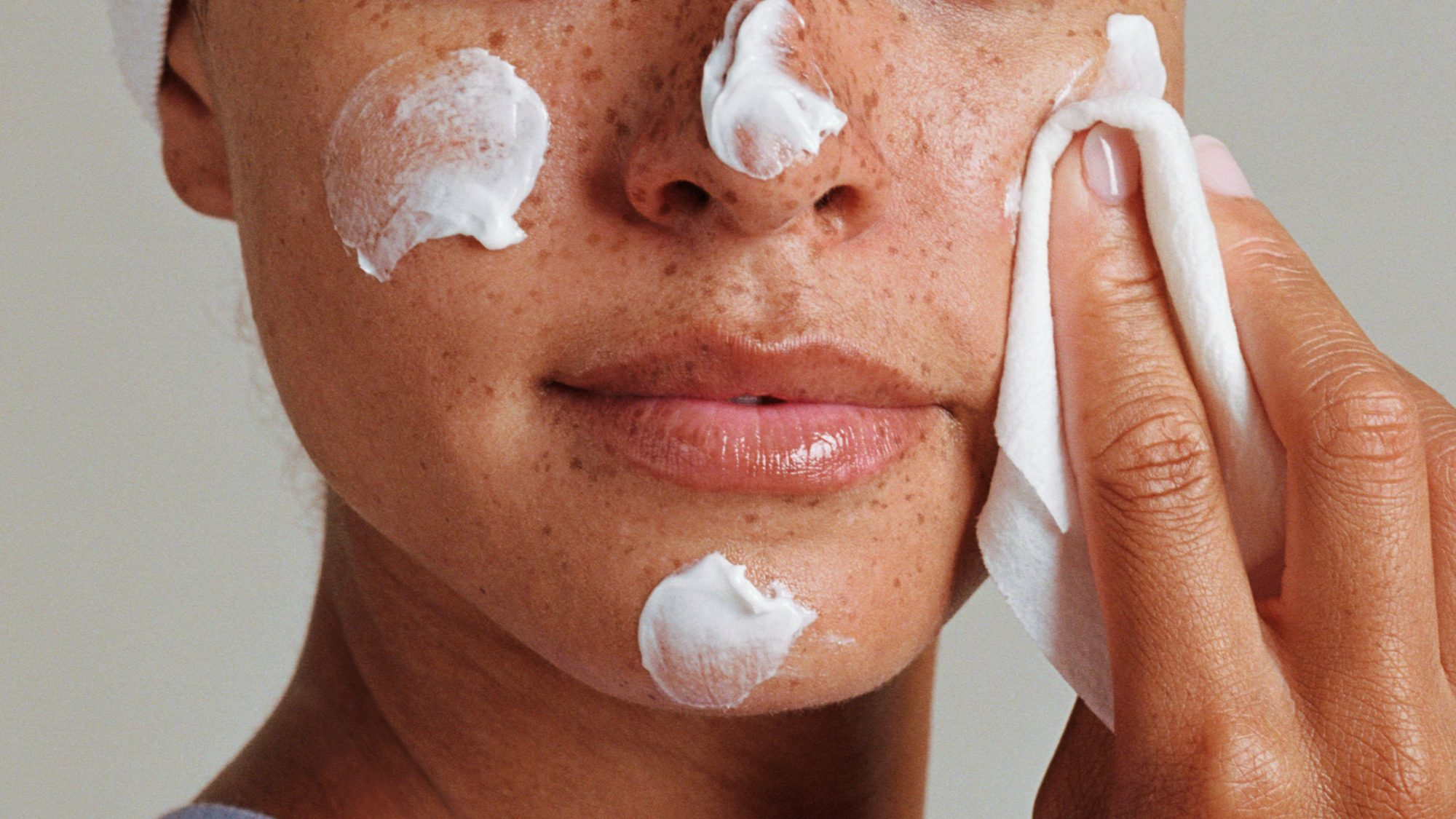 woman putting moisturizer on skin