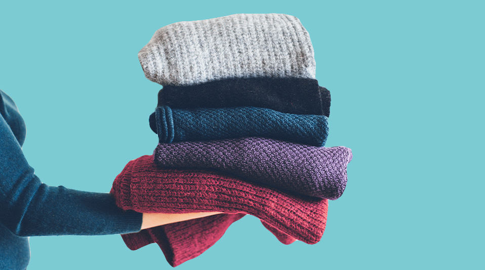 How to Care for Winter Clothes: stack of folded sweaters and scarves