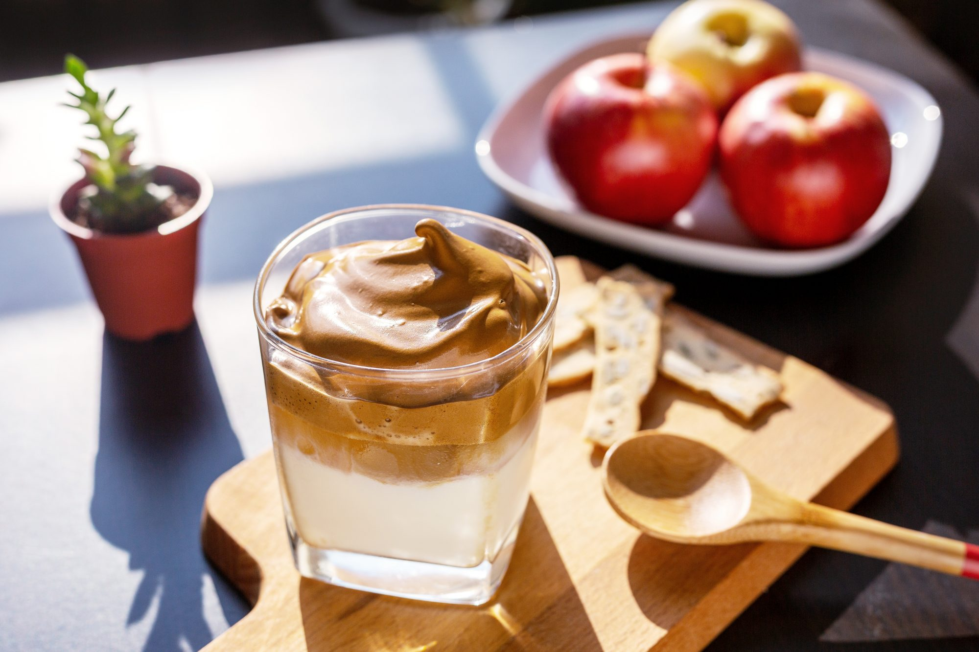 Delicious homemade Iced Dalgona Coffee, a trendy fluffy creamy whipped coffee—served on a table, with a plate of apple as background