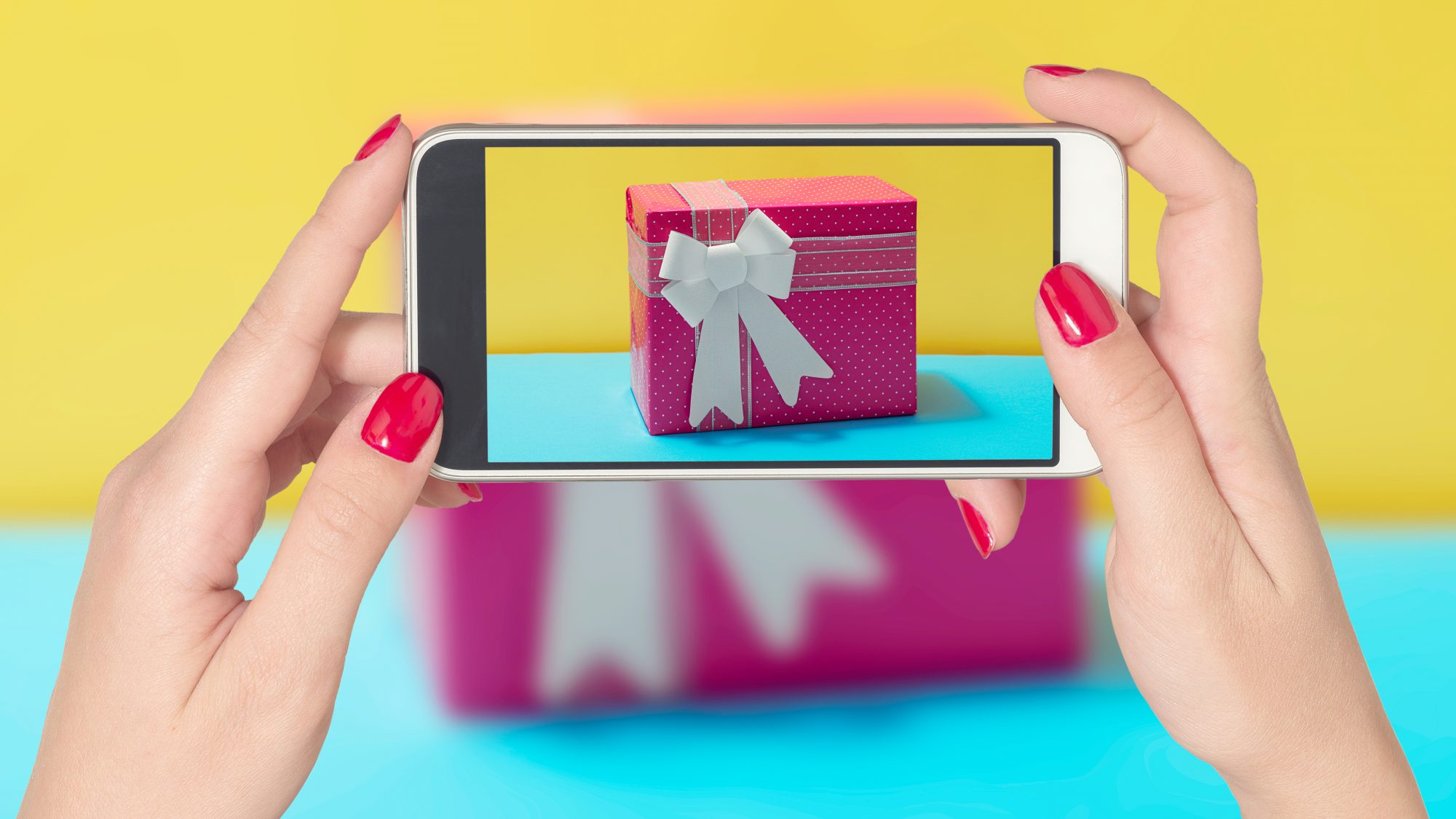 virtual-bridal-shower: woman taking picture of a gift with her phone