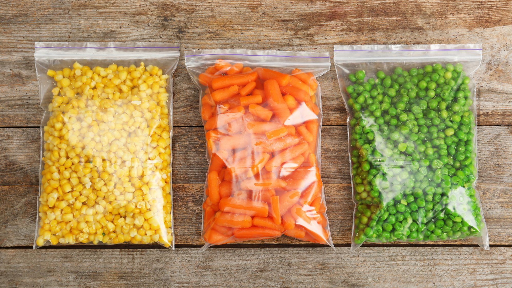 Meal Prep: Plastic bags with frozen vegetables on wooden background, top view