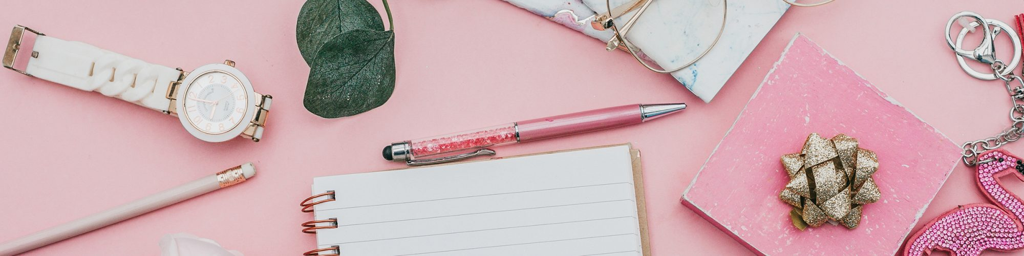 White notebook and pink pen on a pink background