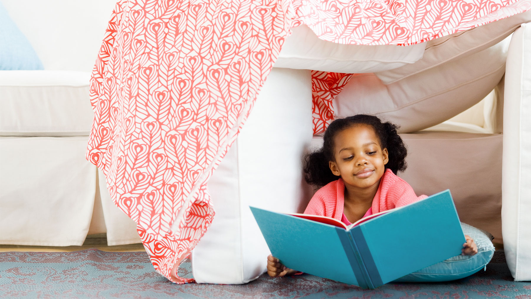How to make a blanket fort - girl reading in blanket fort